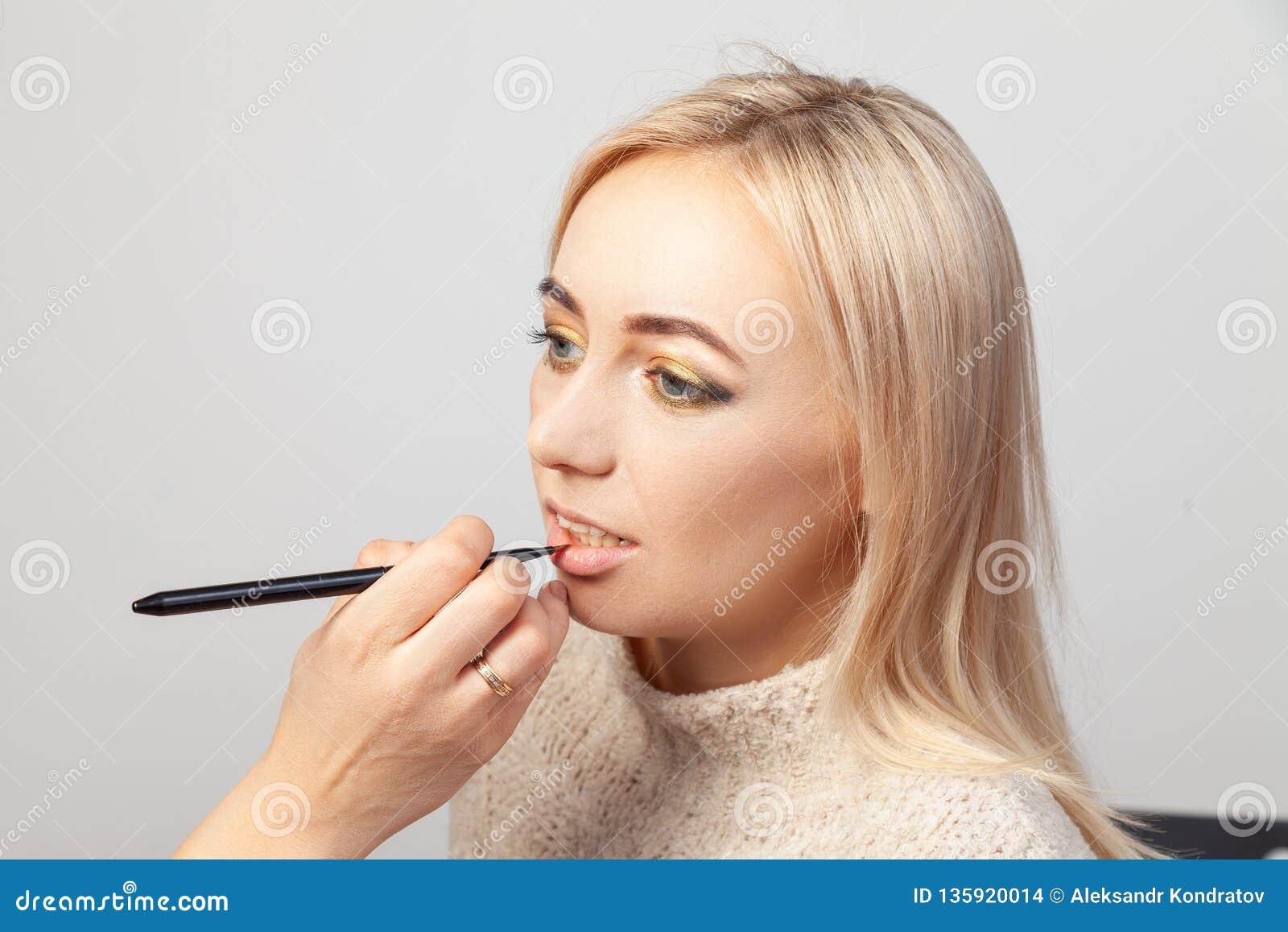 En makeup i en skönhetstudio, en sminkkonstnär med en borste i hennes hand sätter en produkt på kanterna av en blond modell med e