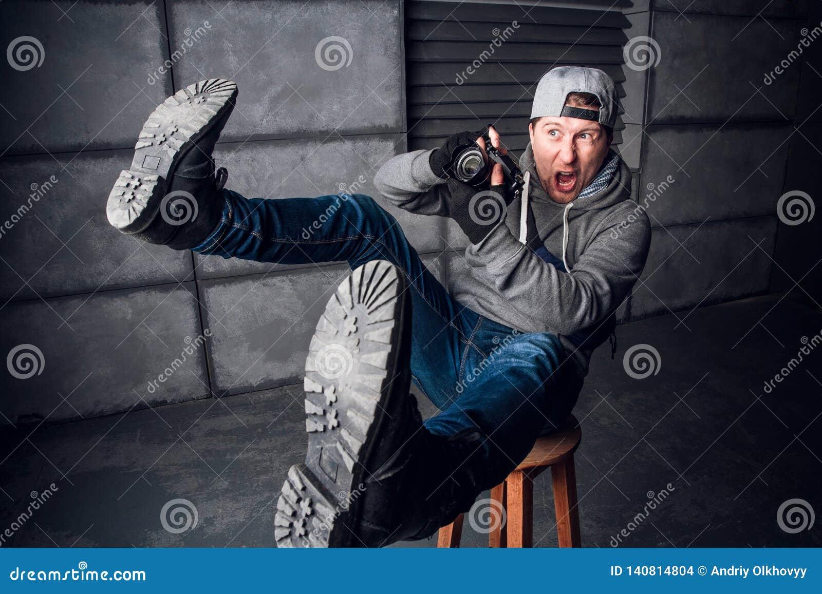 En man är en fotograf med kameran rolig framsida Mörkt - grå bakgrund placera text Fotografen skjuter på