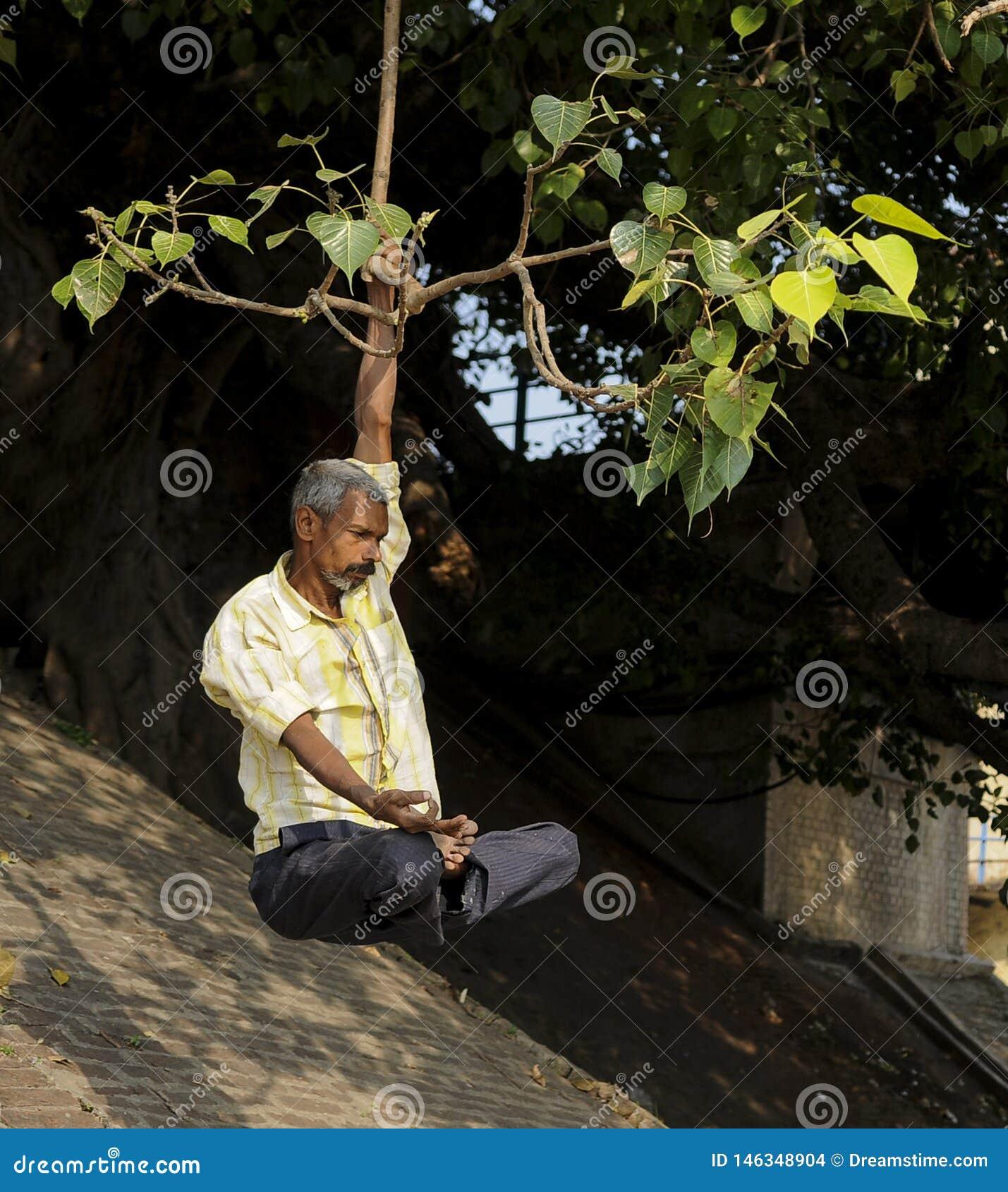 En man öva yoga i Gangesen