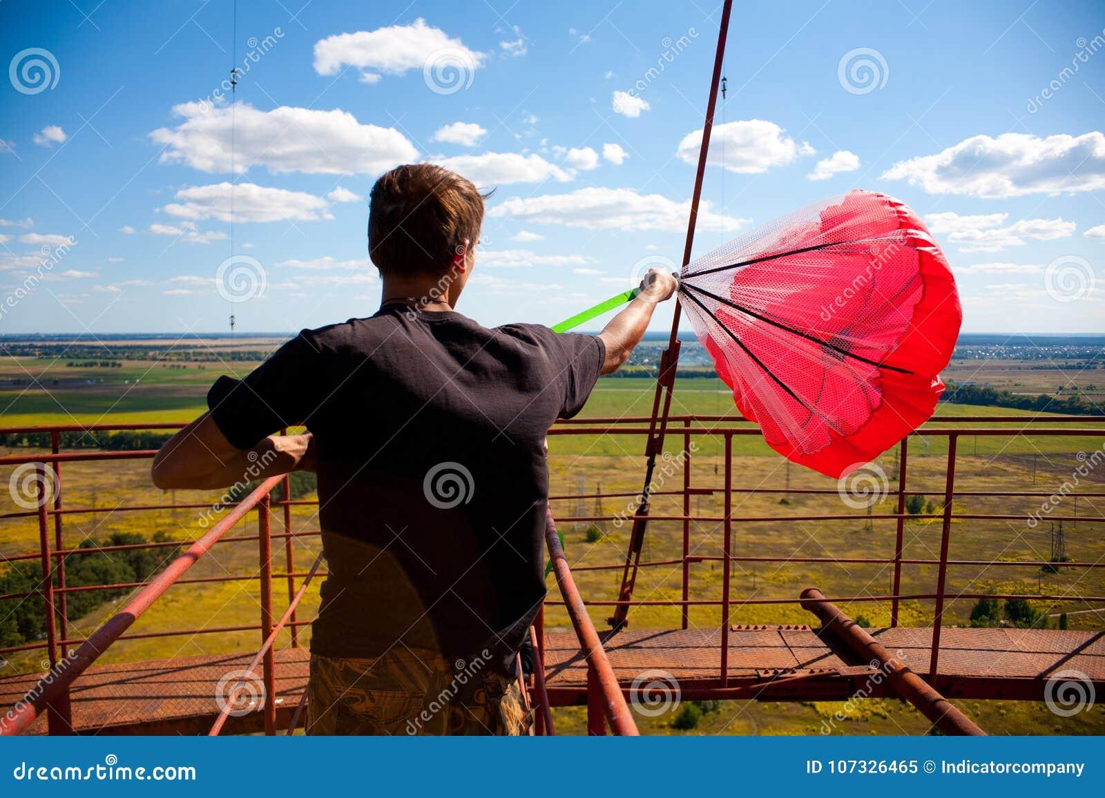 En man förbereder ett rött hoppa fallskärm för grundbanhoppning