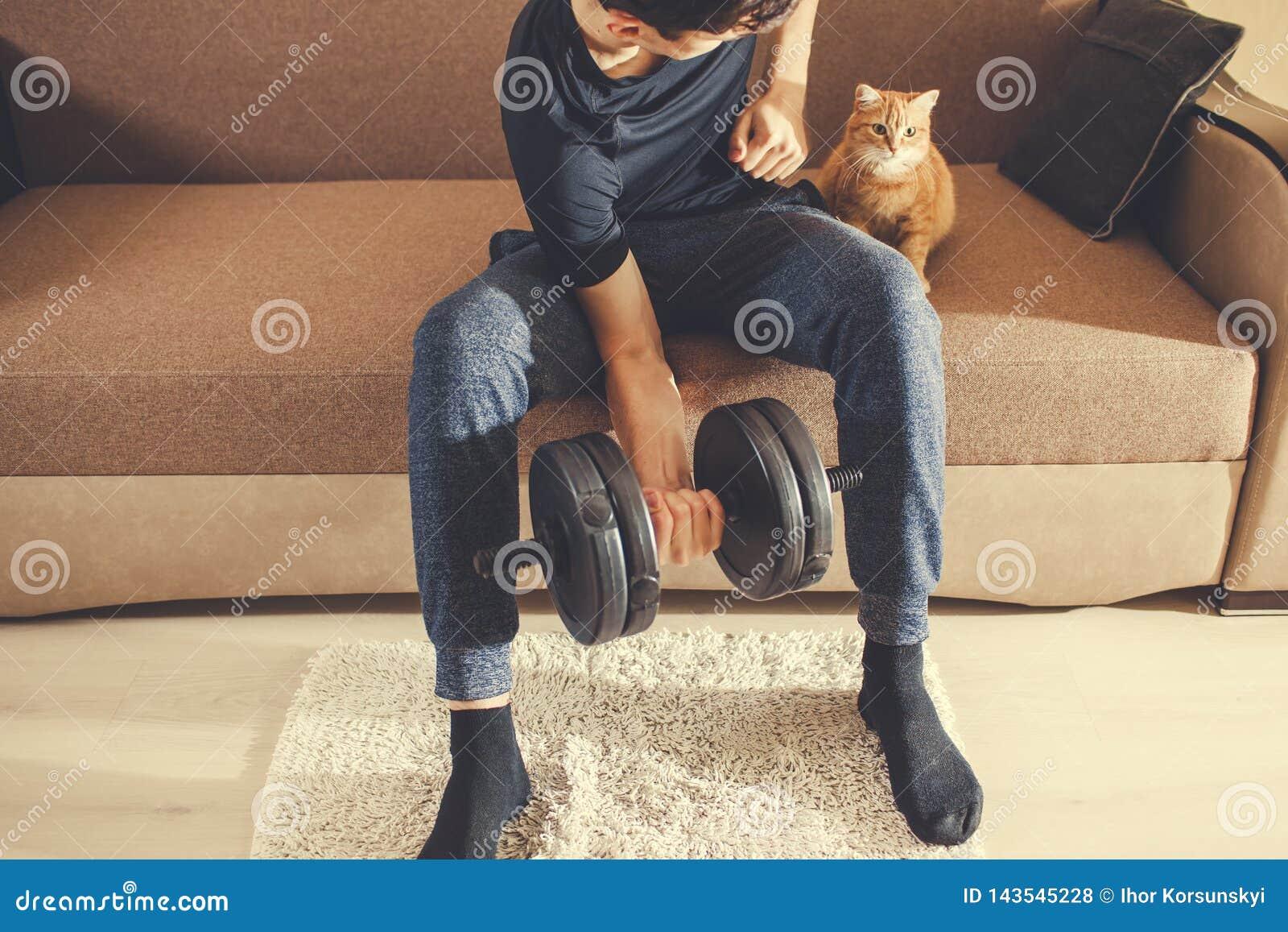 En man går in för sportar hemma med hantlar med en katt