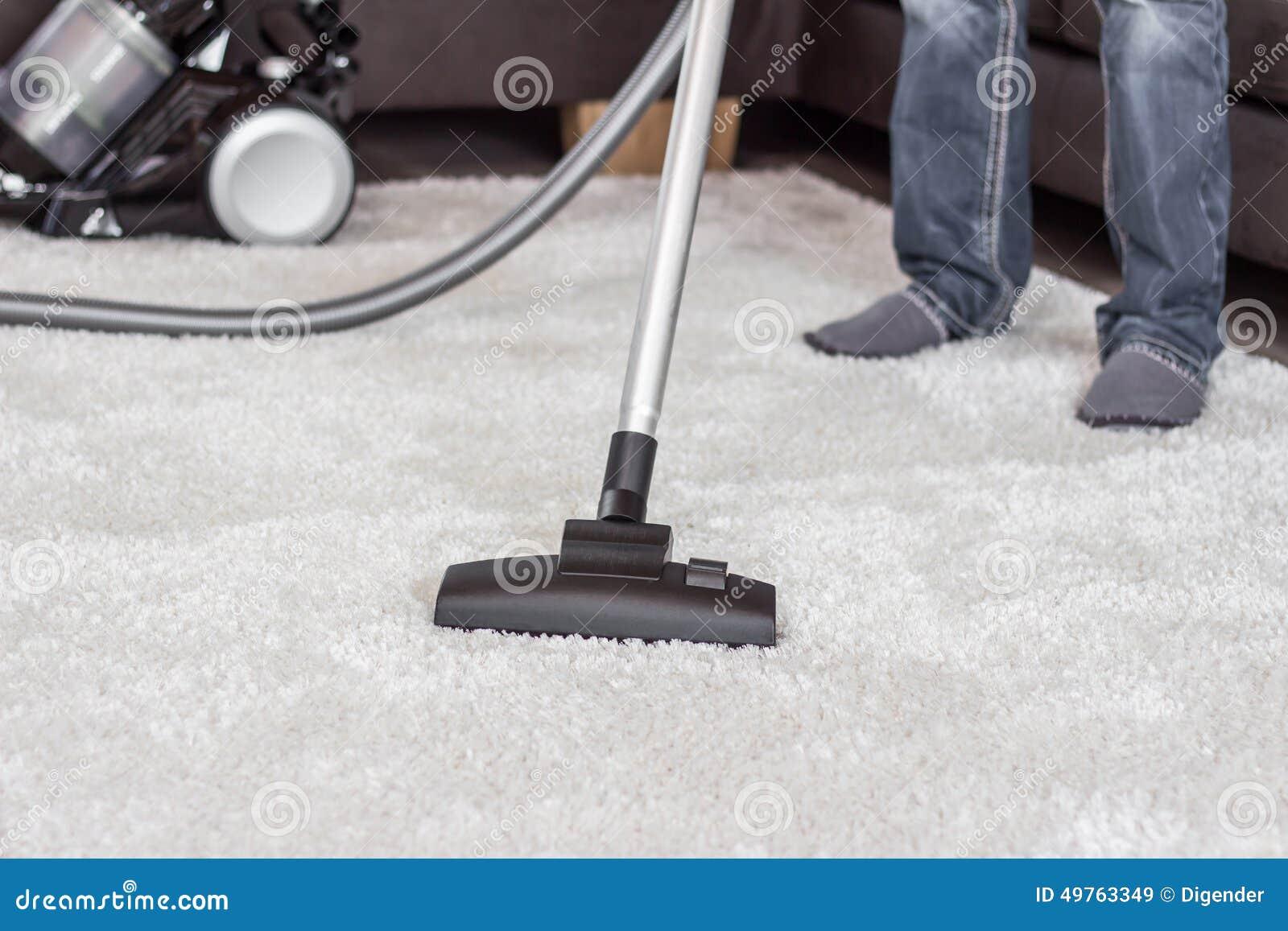 En man gör ren mattan med en dammsugare