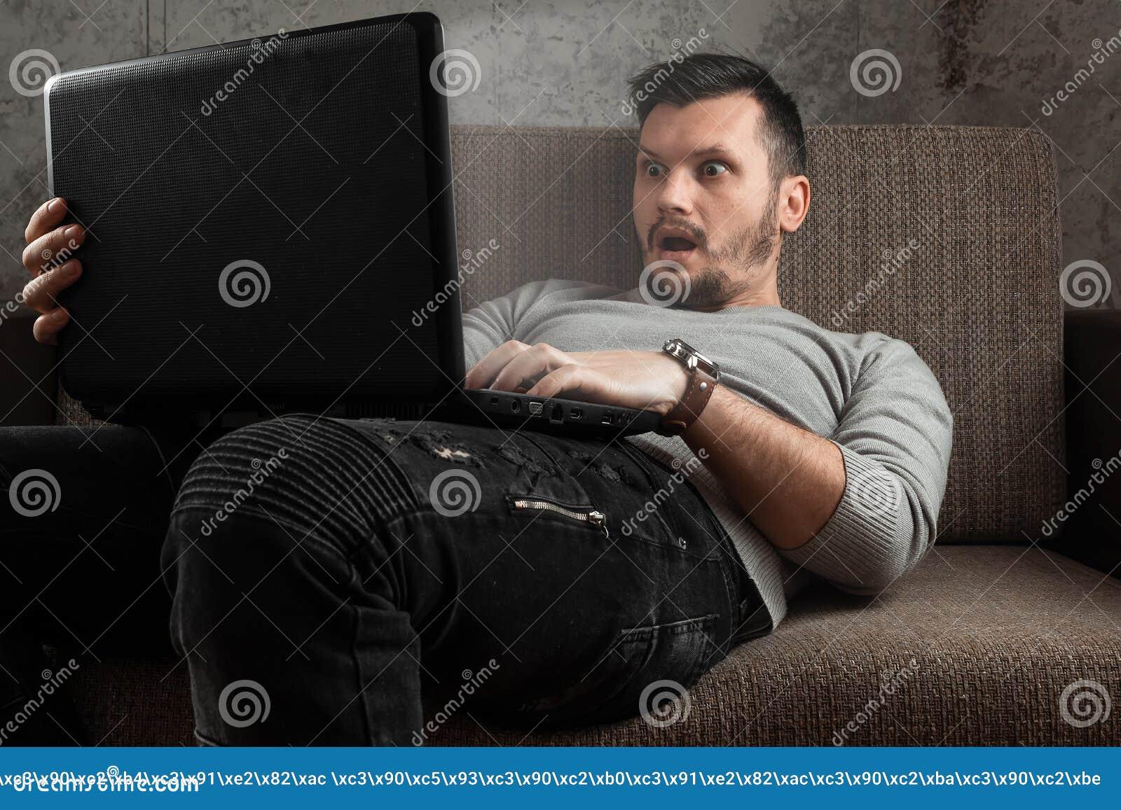 En man h?ller ?gonen p? en vuxen video p? en b?rbar dator, medan sitta p? soffan Begreppet av pornografi, masturbation, manliga b