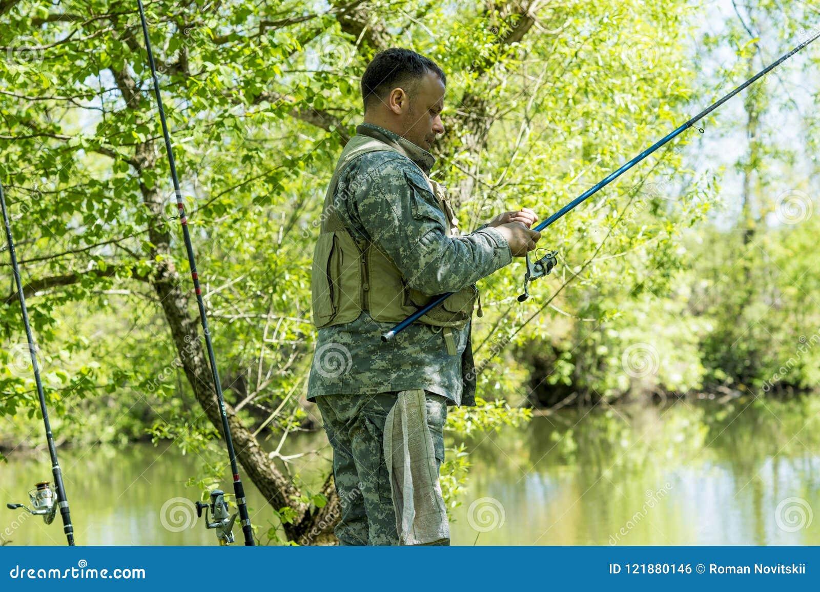 En man i kamouflagemetspö på flodbanken i försommar