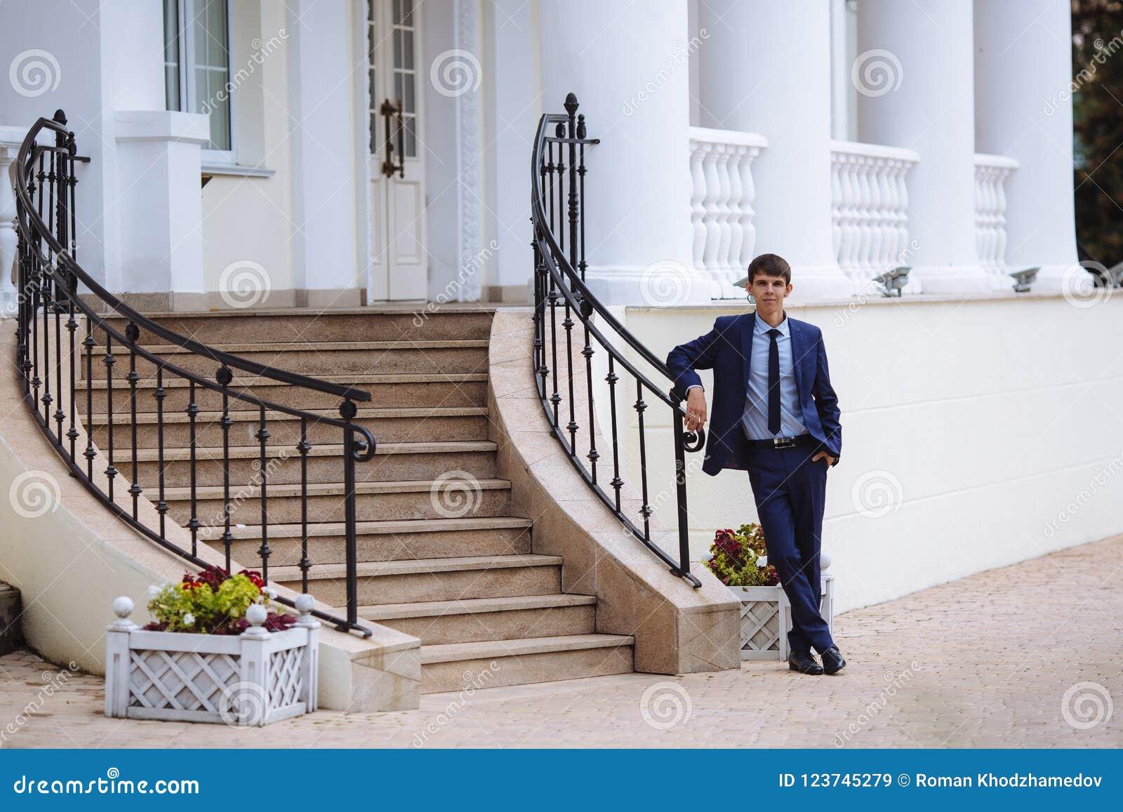 En man i en mörk dräkt för affär står på trappan på gatan med hans korsade ben och väntar på någon, honom