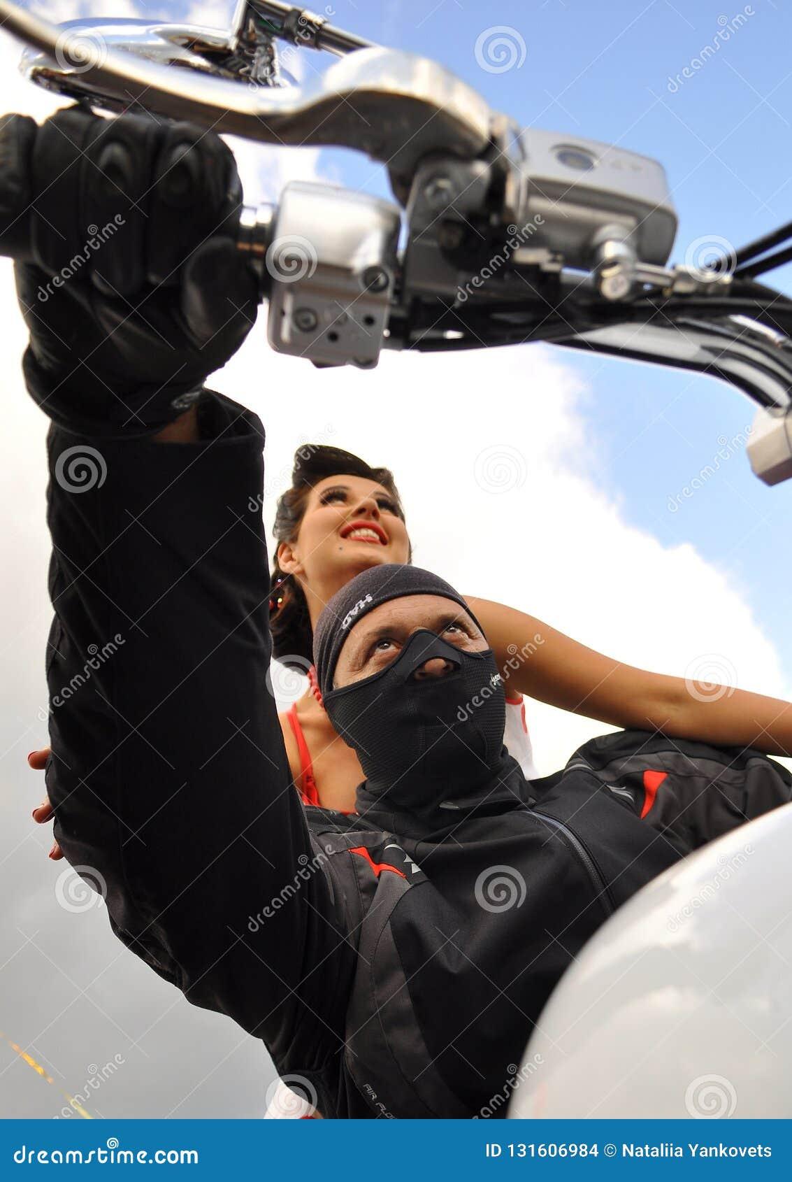 En man i en svart maskering sitter bak hjulet av en vit motorcykel bak honom sitter en härlig flicka på en bakgrund av den blåa h