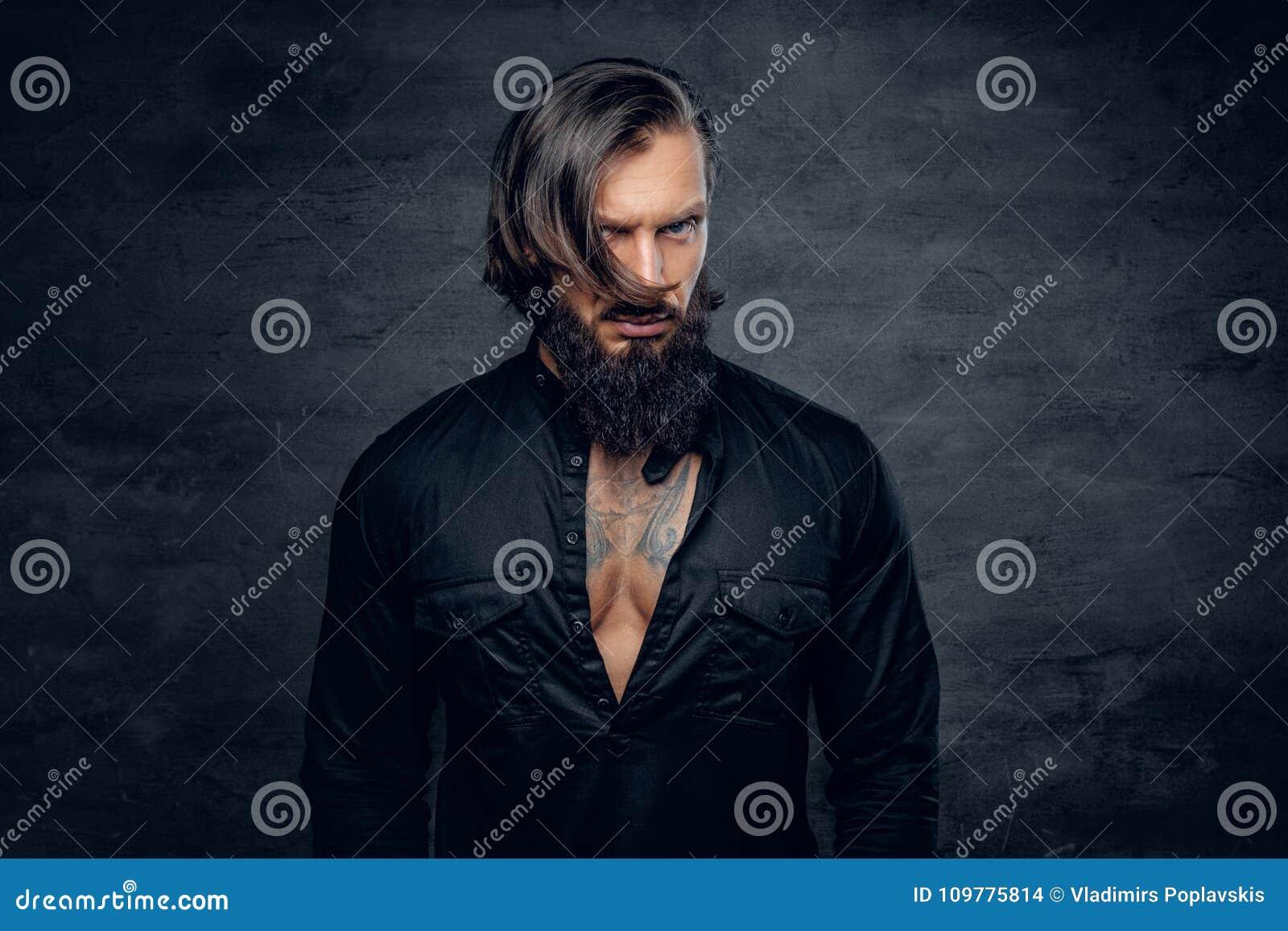 En man i svart skjorta med tatueringen på hans bröstkorg