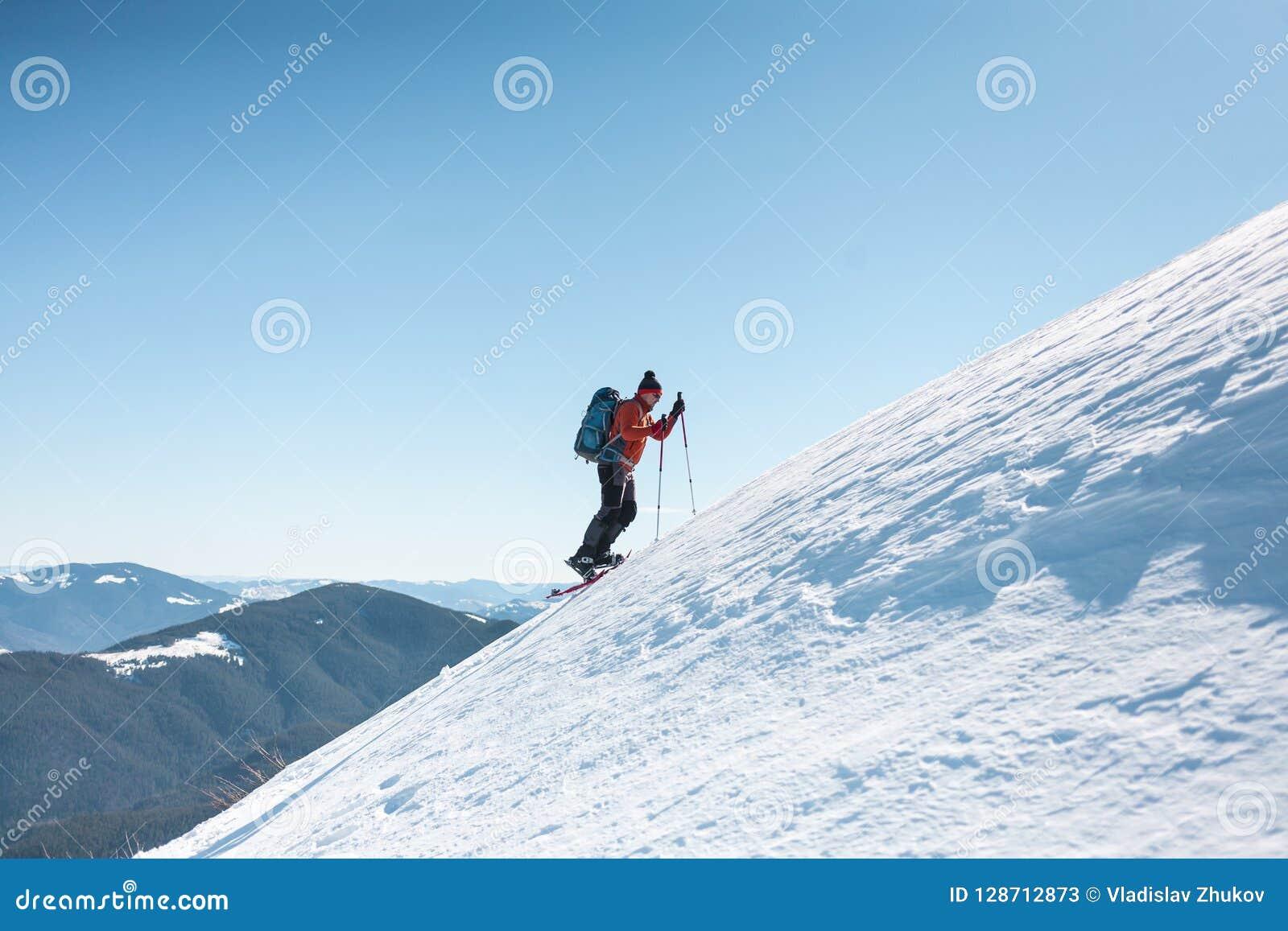 En man klättrar till överkanten av berget