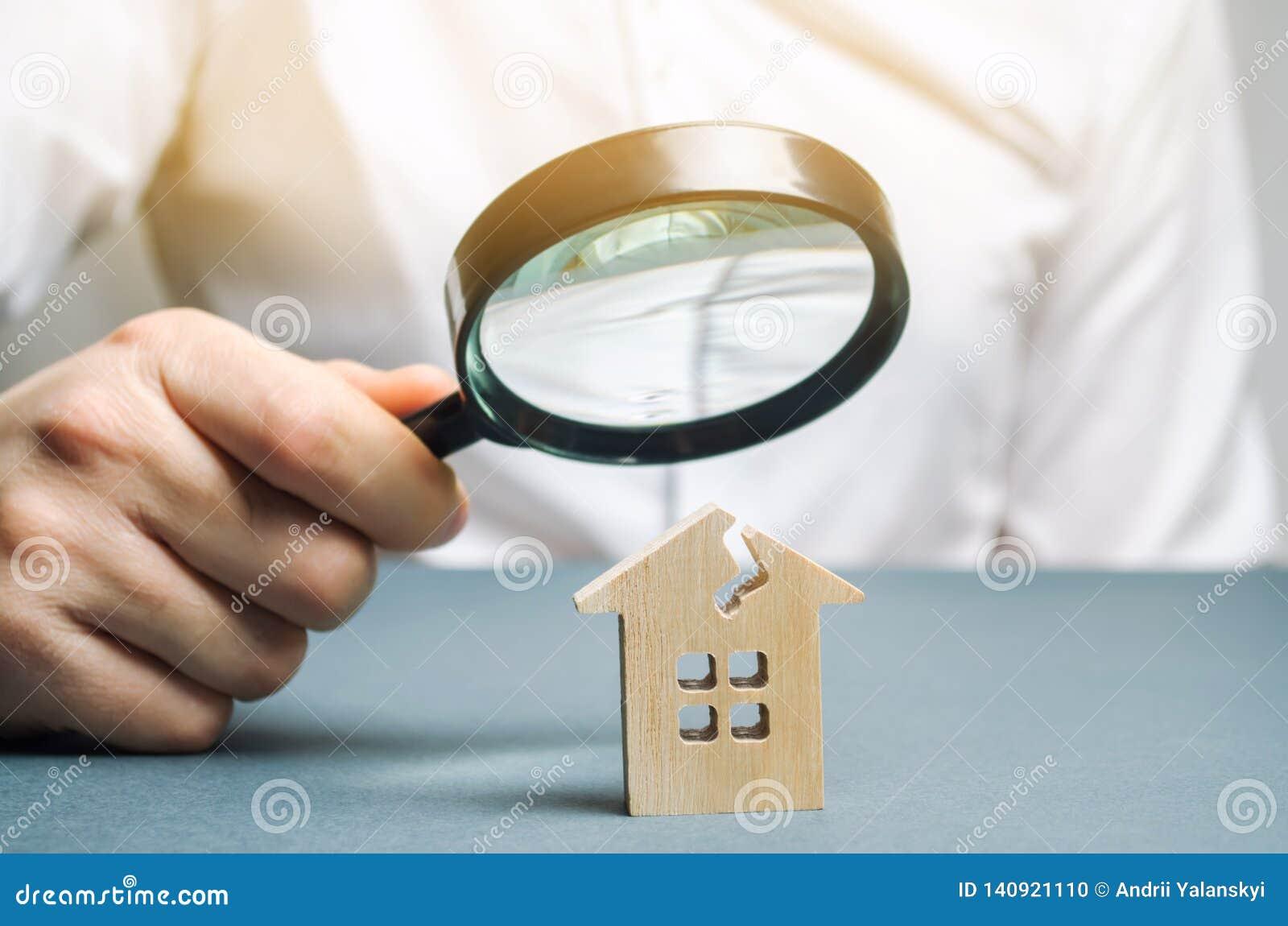 En man med ett förstoringsglas ser ett hus med en spricka Risker för hem och för försäkring för skadebedömning
