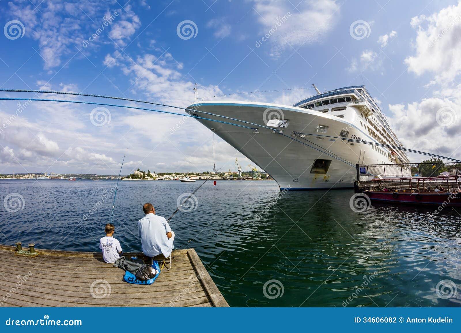 En man och ett pojkefiske i porten av Sevastopol
