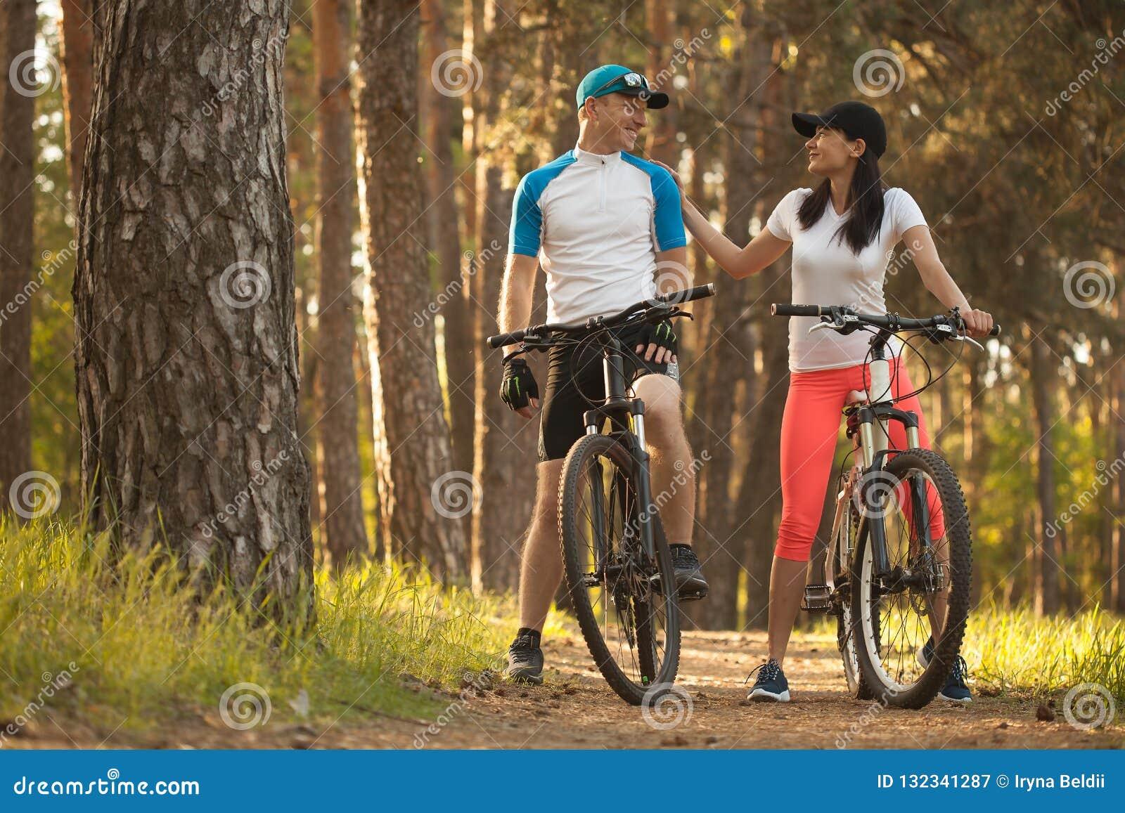 En man och en kvinna gå att cykla i träna Cykel till naturen