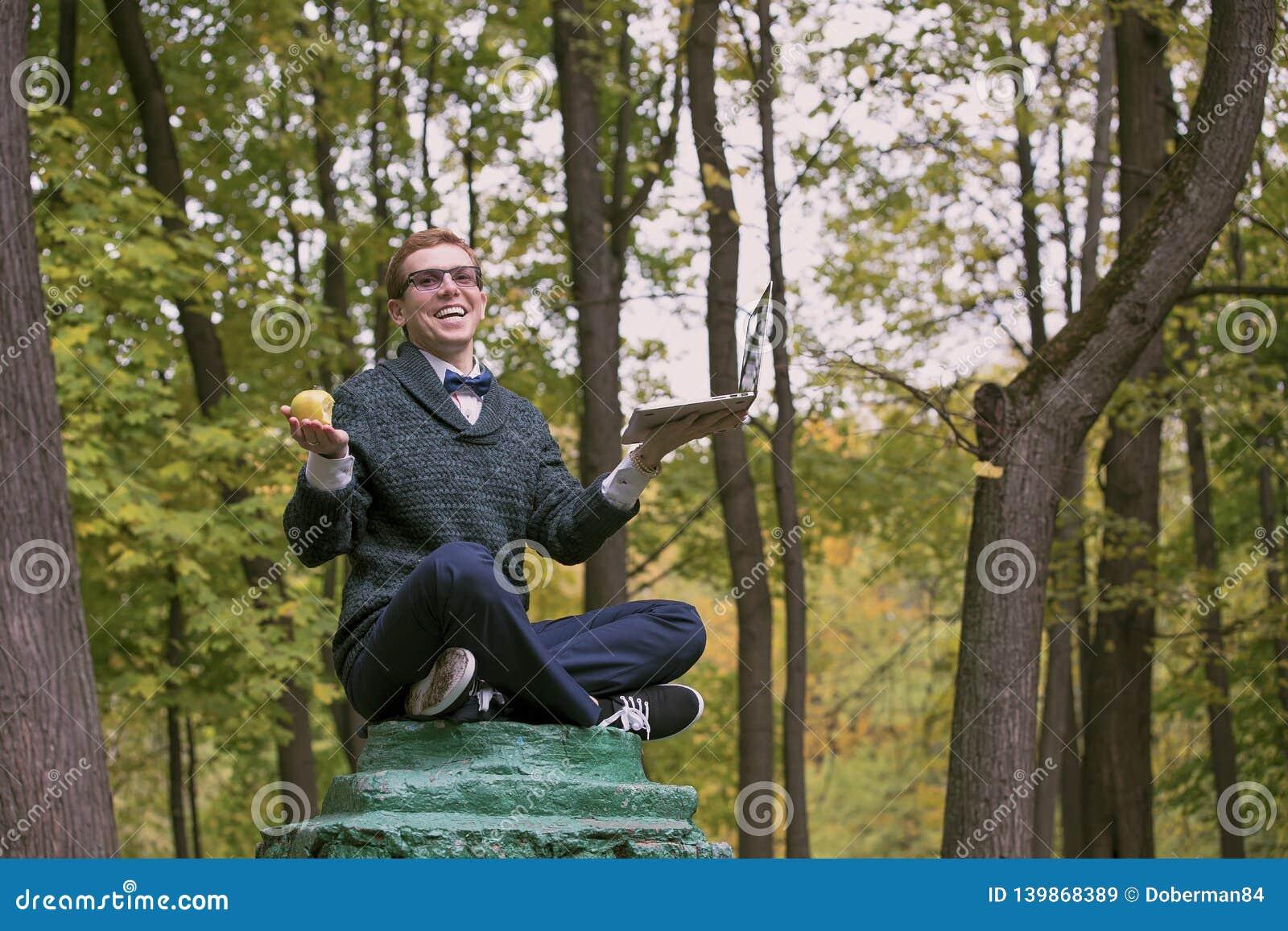 En man på en sockel, som låtsar för att vara en staty i, poserar av en filosof med äpplet och bärbara datorn i hösten parkerar
