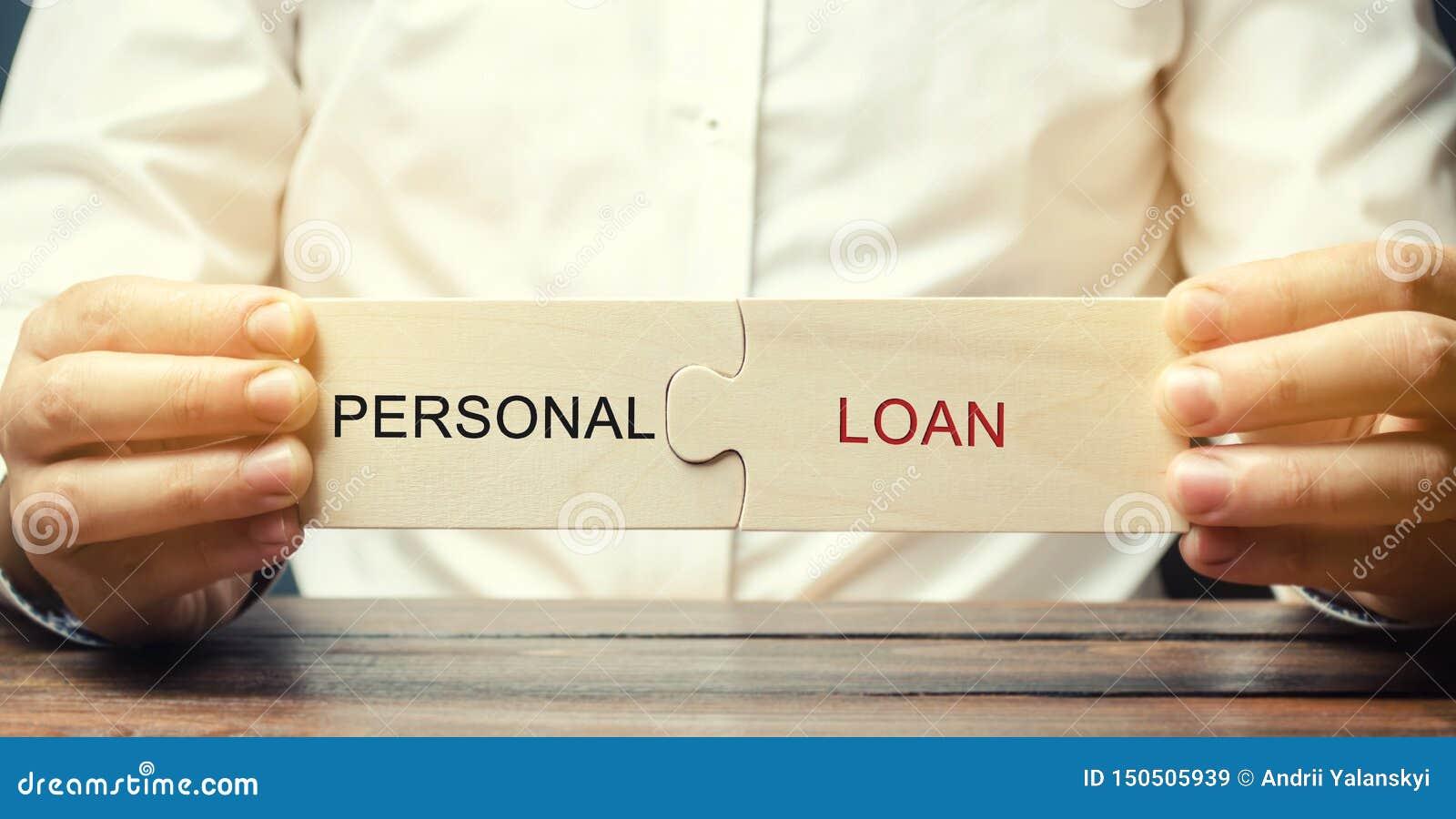 En man samlar träpussel med det personliga lånet för ordet Ett lån utfärdade vid en bank till individer för konsumentavsikter int