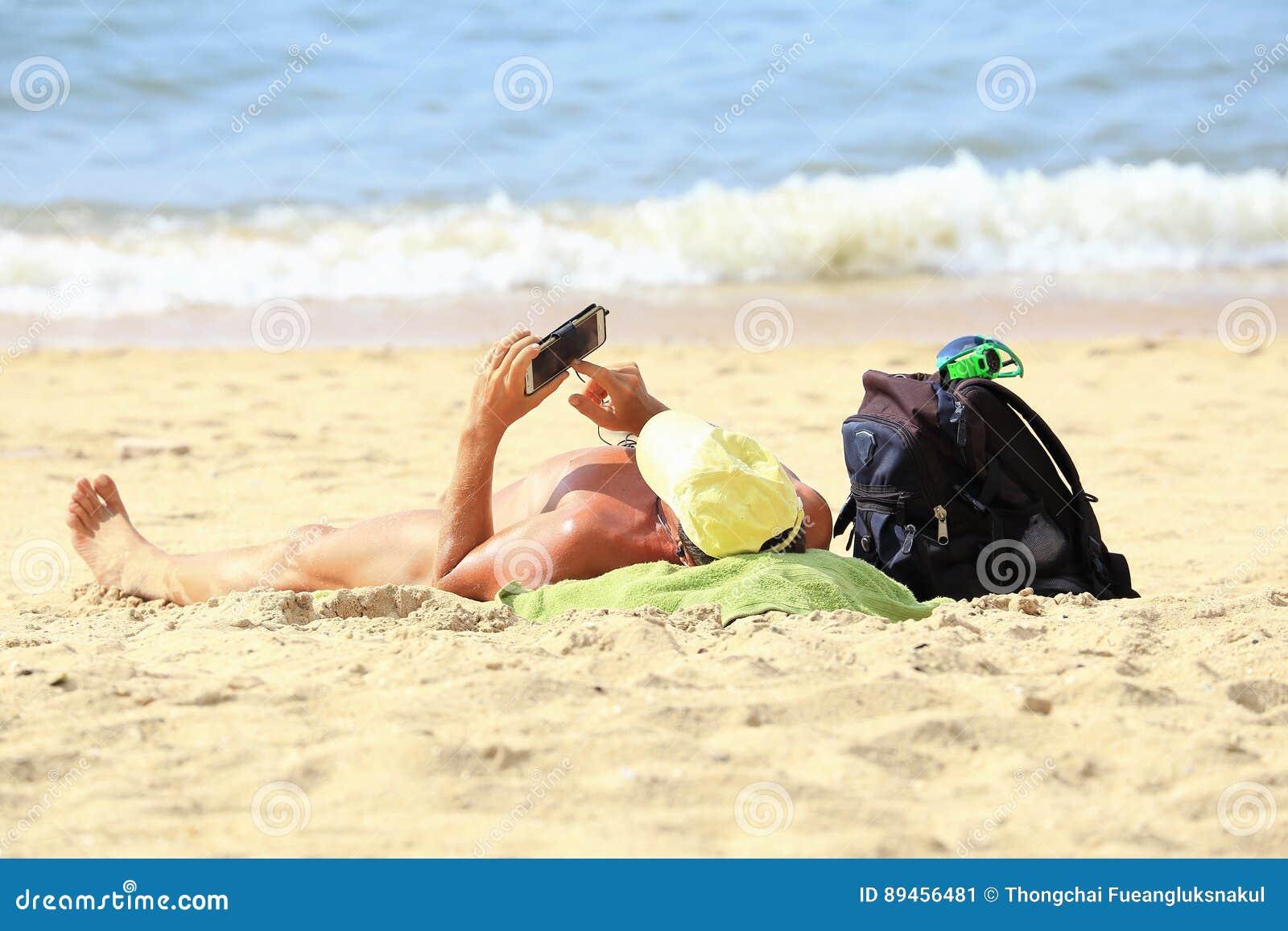 En man solbadar på stranden och trycker på mobilen, Pattaya Thailand