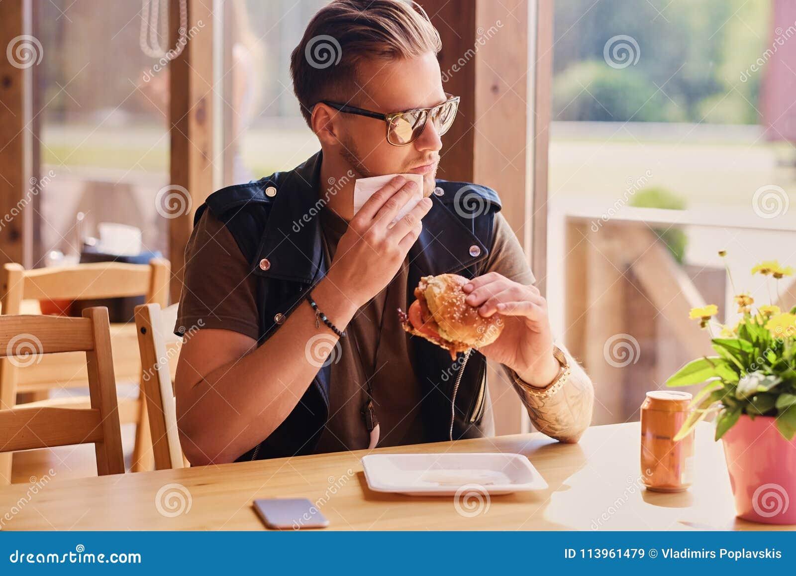 En man som äter en strikt vegetarianhamburgare