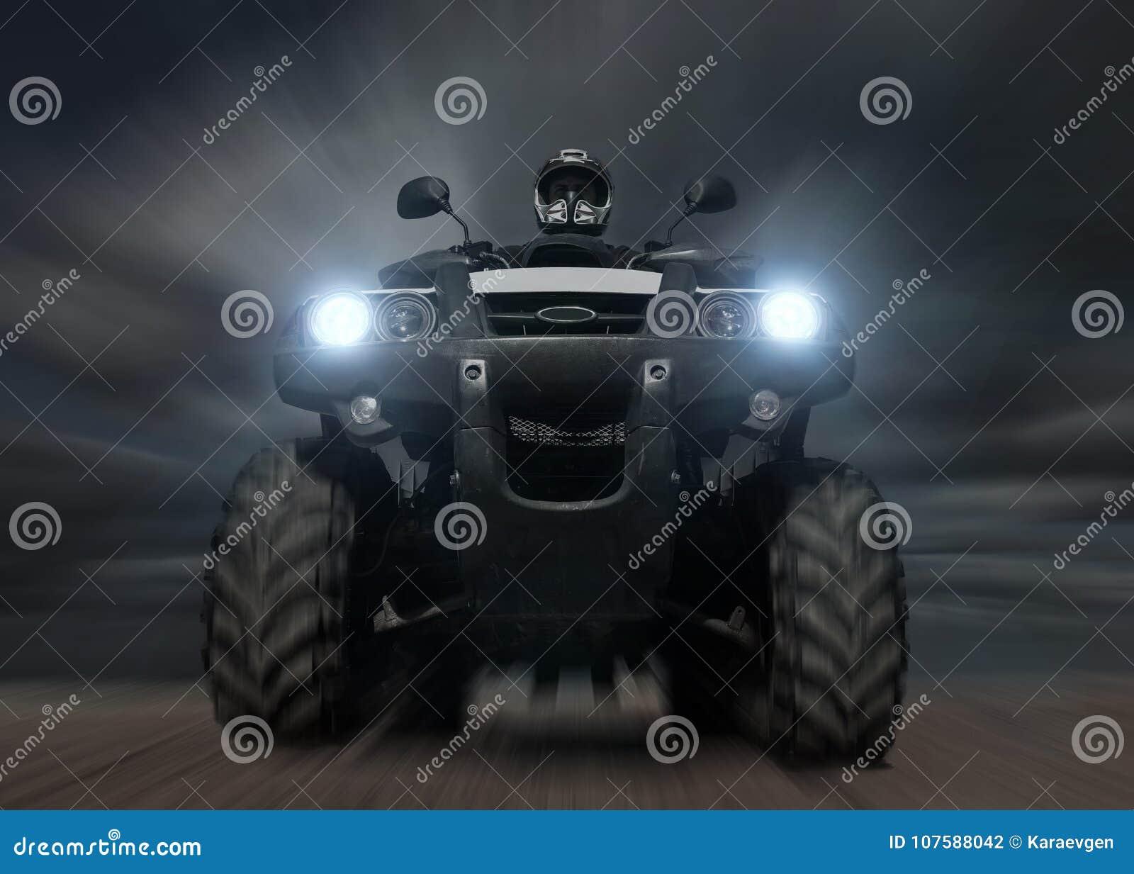 En man som rider ATV i sand i skyddande hjälm