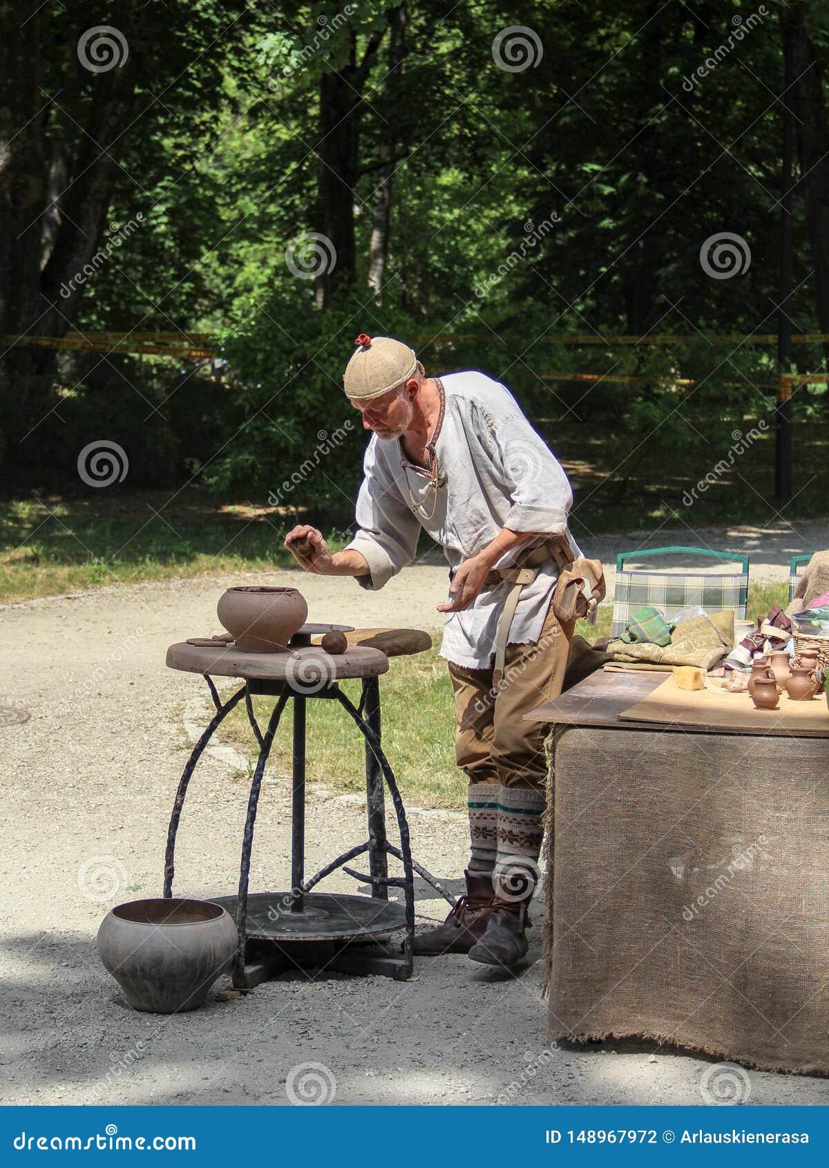 En man som visar gamla keramikerhantverk