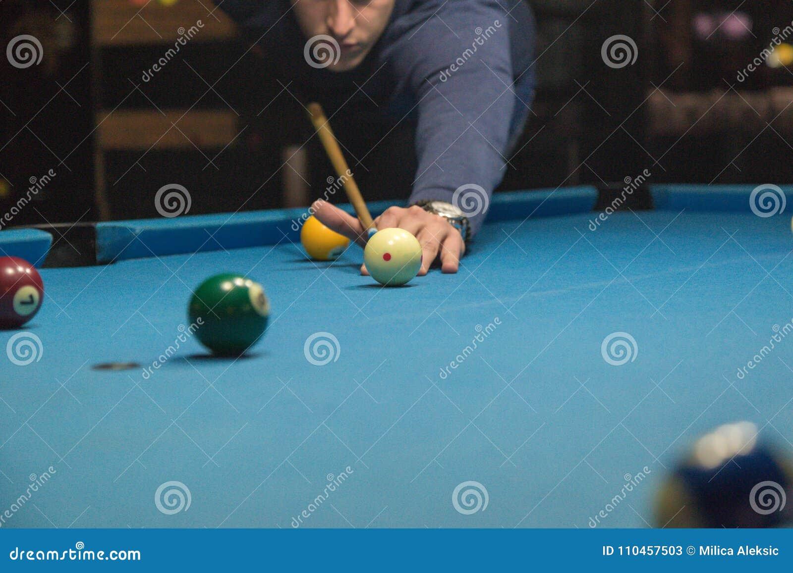 En man spelar en billiard på klubban
