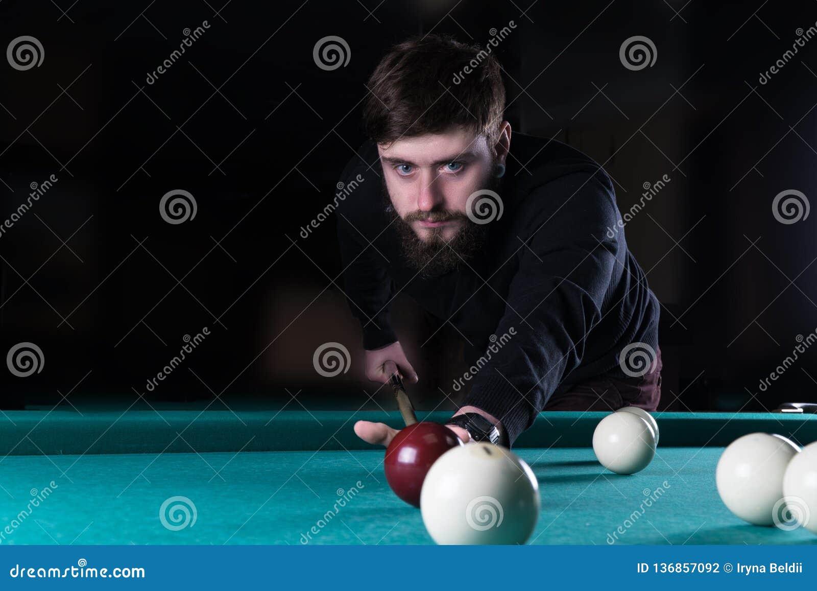 En man spelar en lek av pölen pöl göra poäng bollen