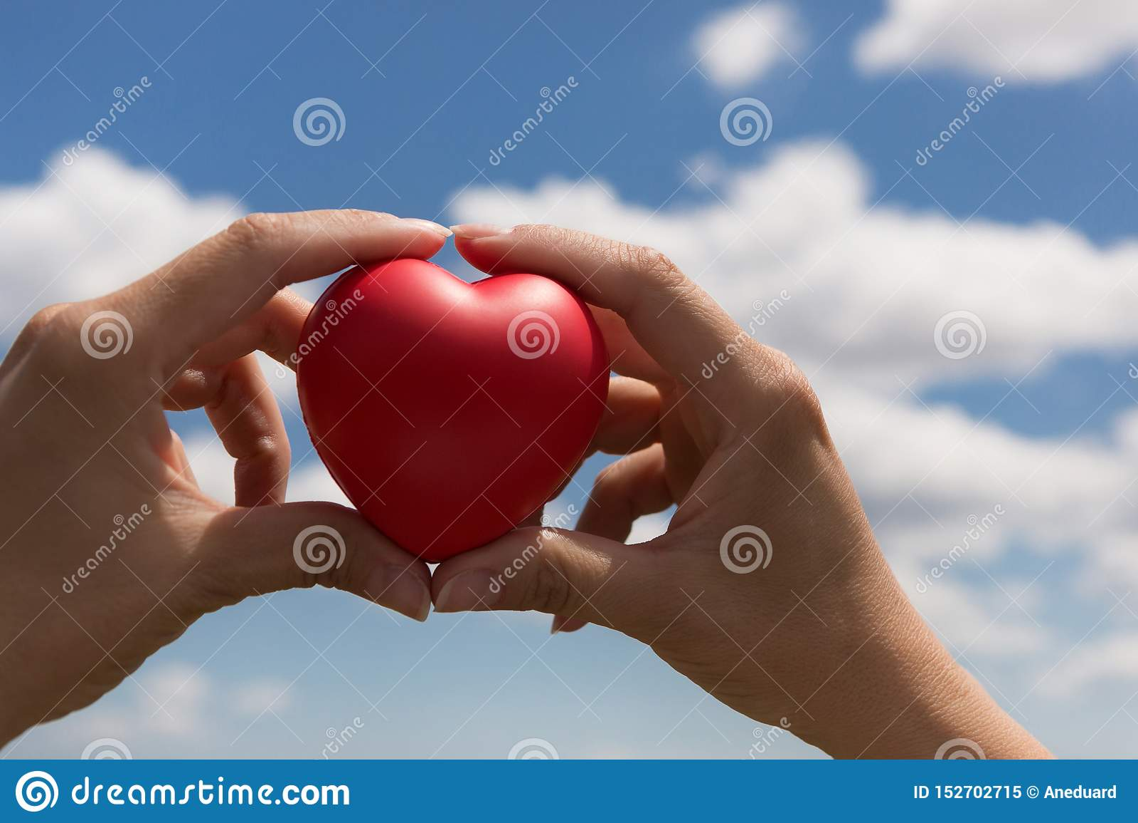 En manos femeninas un corazón volumétrico rojo, como símbolo de la vida y del amor, contra el cielo azul con las nubes