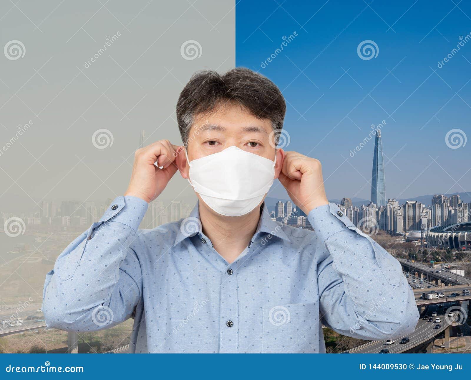En medelålders man som mycket bär en maskering i bakgrunden av en stad av fint damm