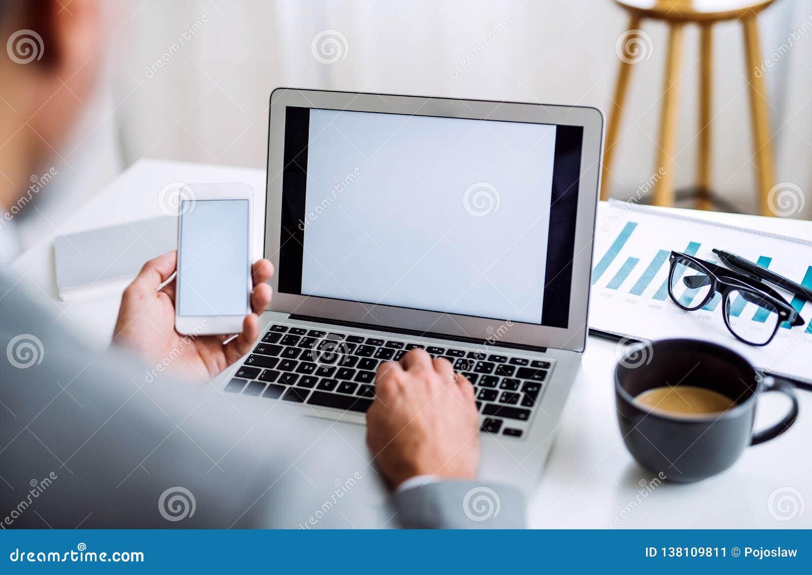 En midsection av affärsmannen med smartphonen och bärbara datorn som sitter på tabellen som arbetar