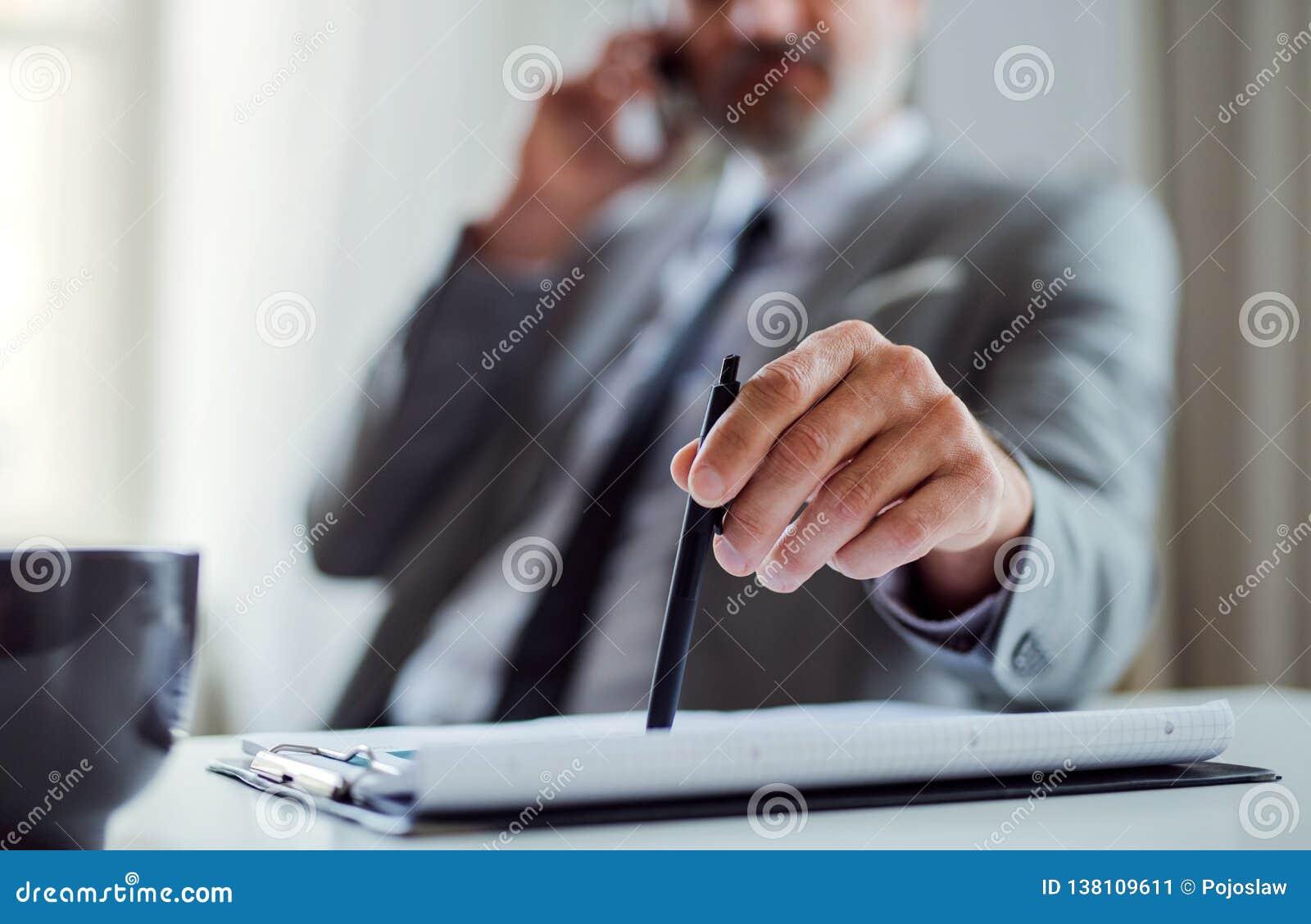 En midsection av affärsmannen med smartphonen som sitter på tabellen som gör en påringning