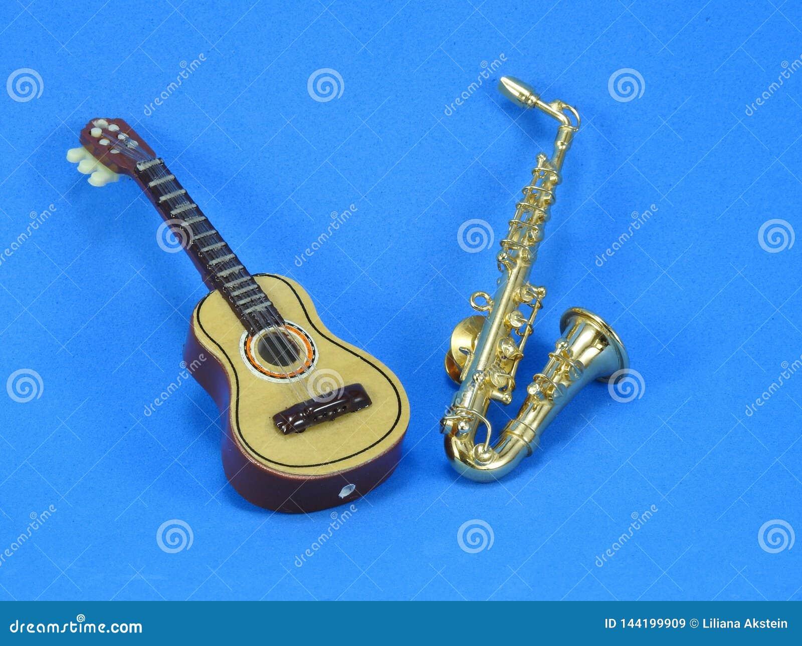 En miniatyrgitarr och saxofon p? bl? bakgrund
