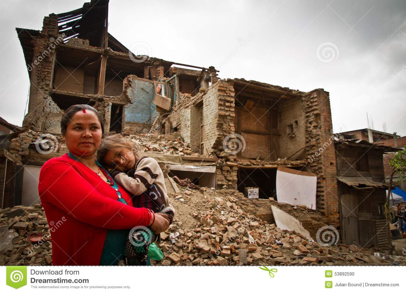 En moder och ett barn utanför en jordskalv fördärvade huset i Bhaktap