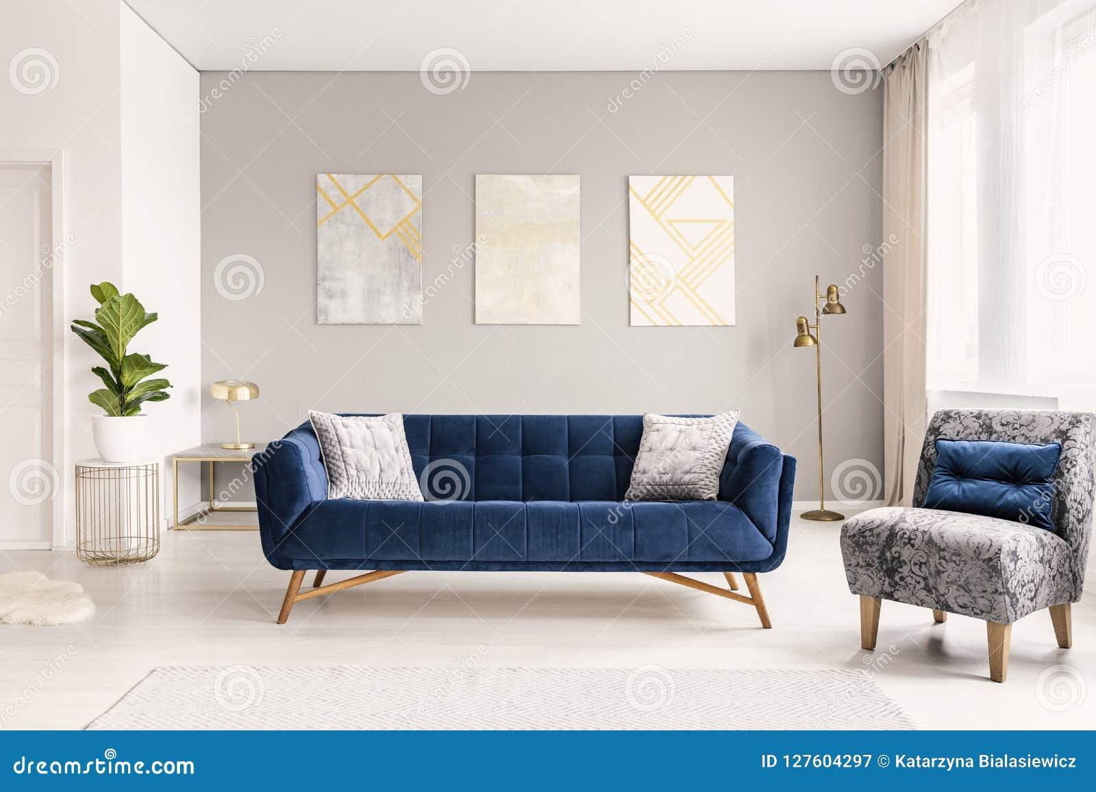 En modern vardagsruminre av en lyxig hotelllägenhet med en märkes- soffa, en fåtölj och konstgarneringar Verkligt foto