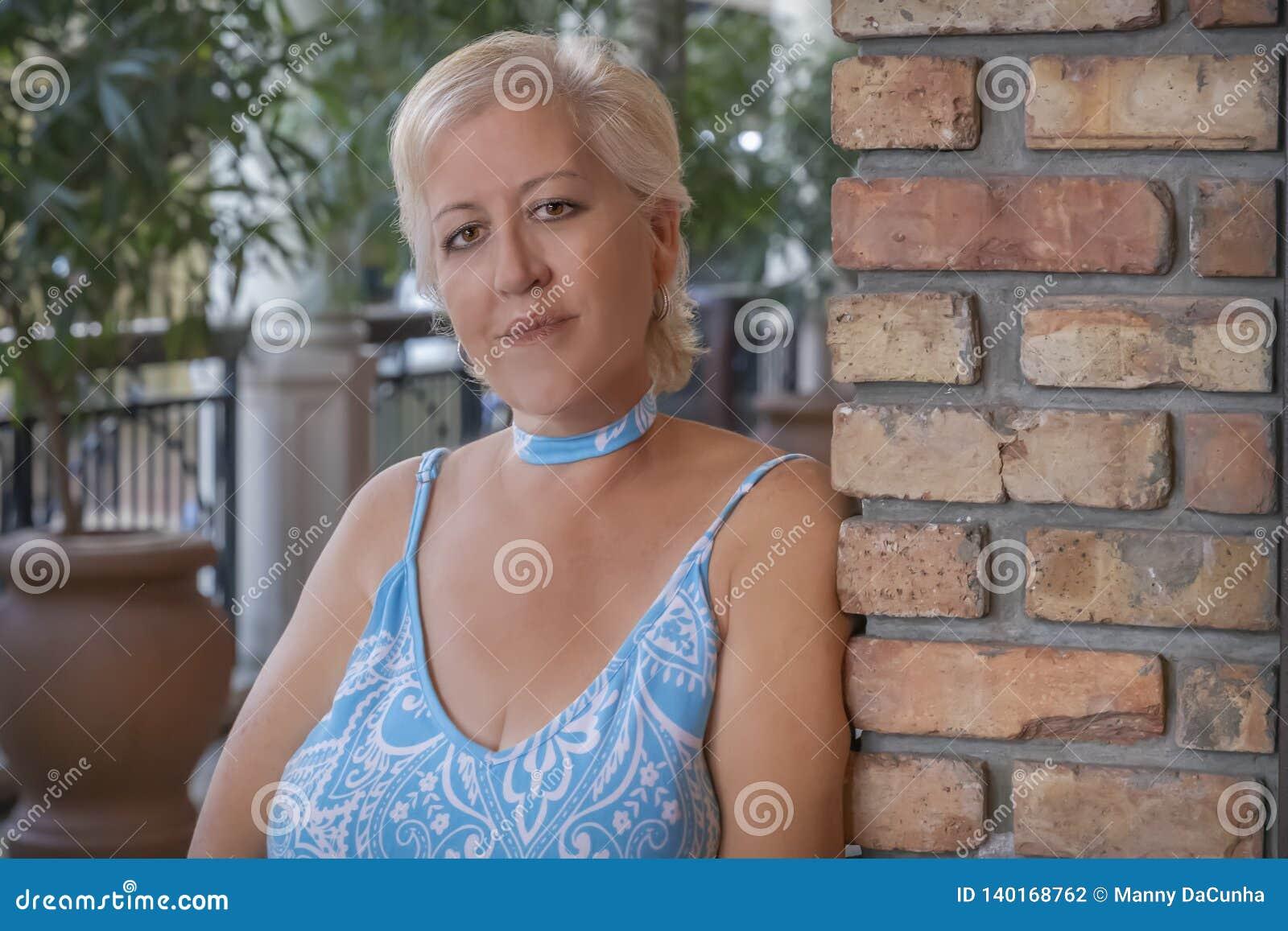 En mogen blond kvinna lutar på en tegelstenvägg som ser kameran med ett leende