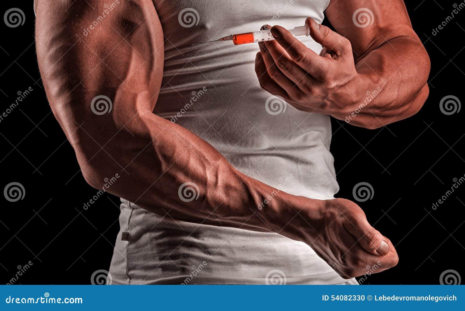 En muskulös man med en injektionsspruta