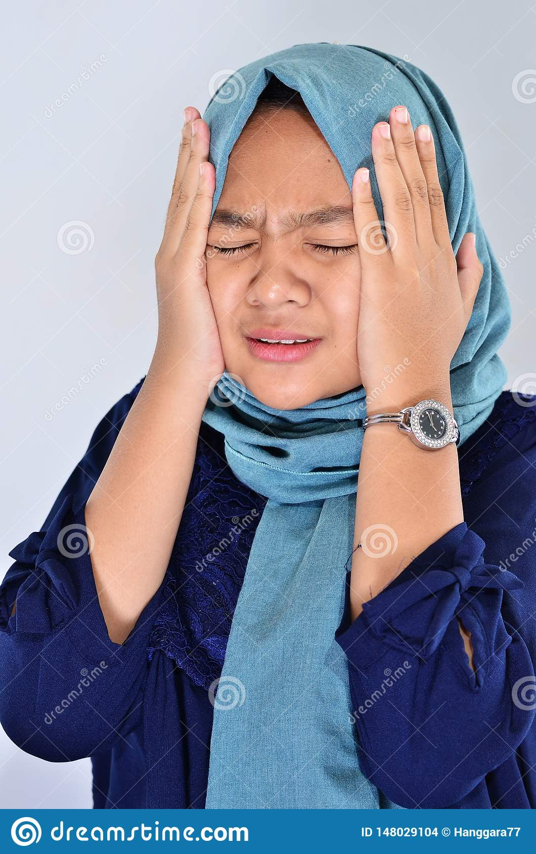 En muslimsk kvinna i skrik för en hijab med att rymma hennes framsida genom att använda hennes händer Den asiatiska flickan tryck