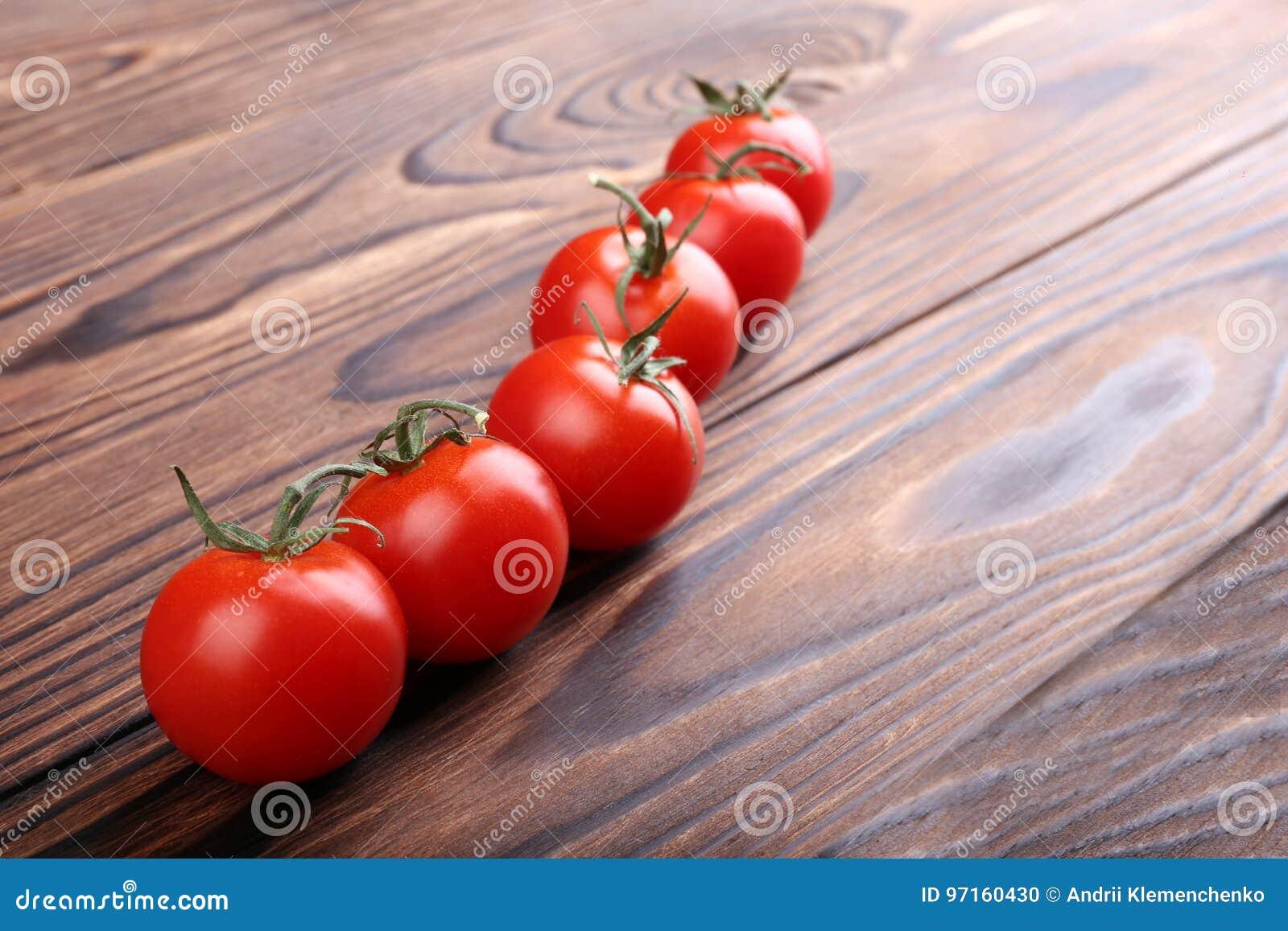 En närbild av nya röda tomater Färgrika tomater på en träbakgrund Organiska salladingredienser Röda körsbärsröda tomater