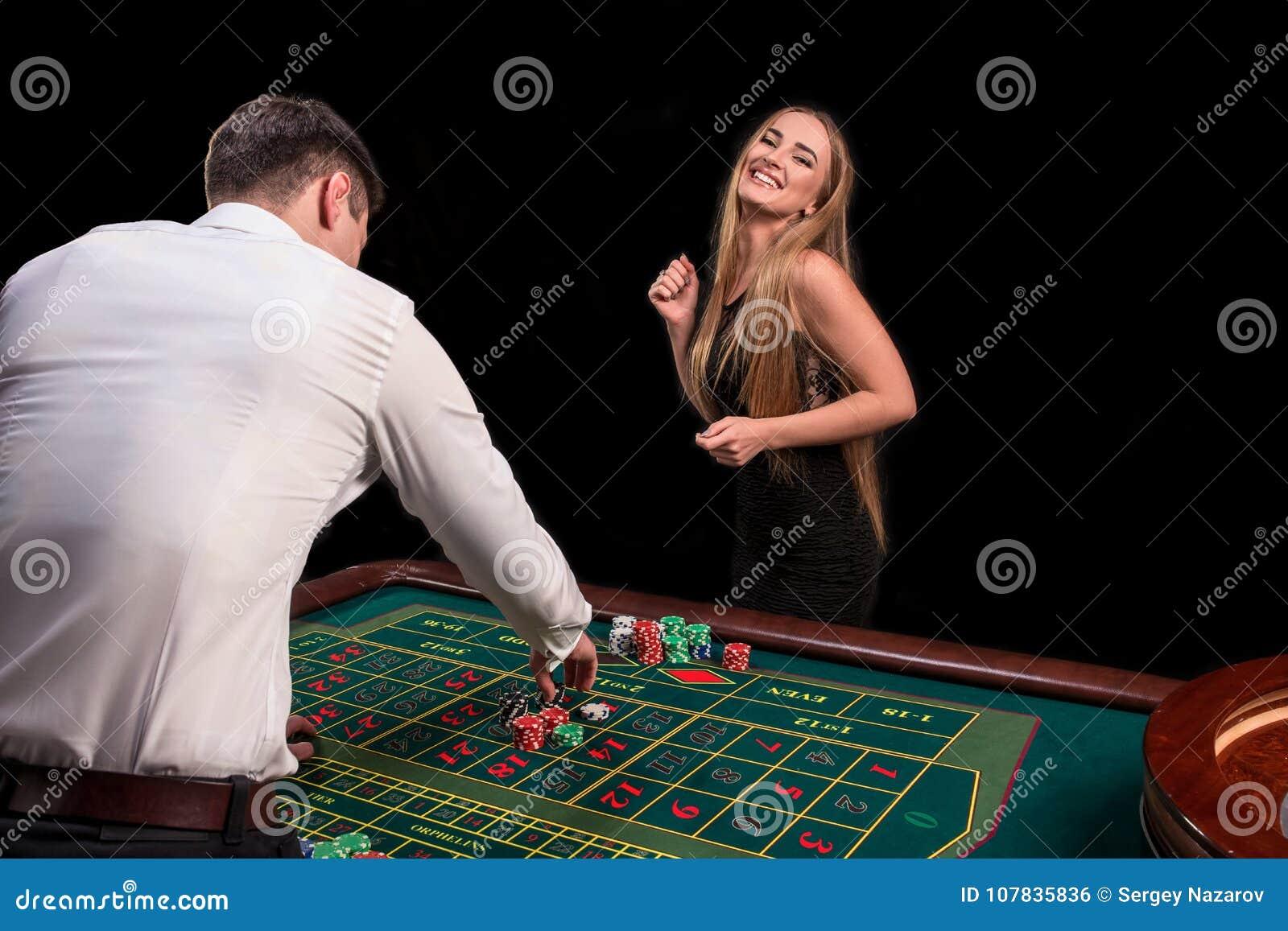 En närbild på baksidan av croupier i en vit skjorta, bilden av den gröna kasinotabellen med rouletten och chiper, rich