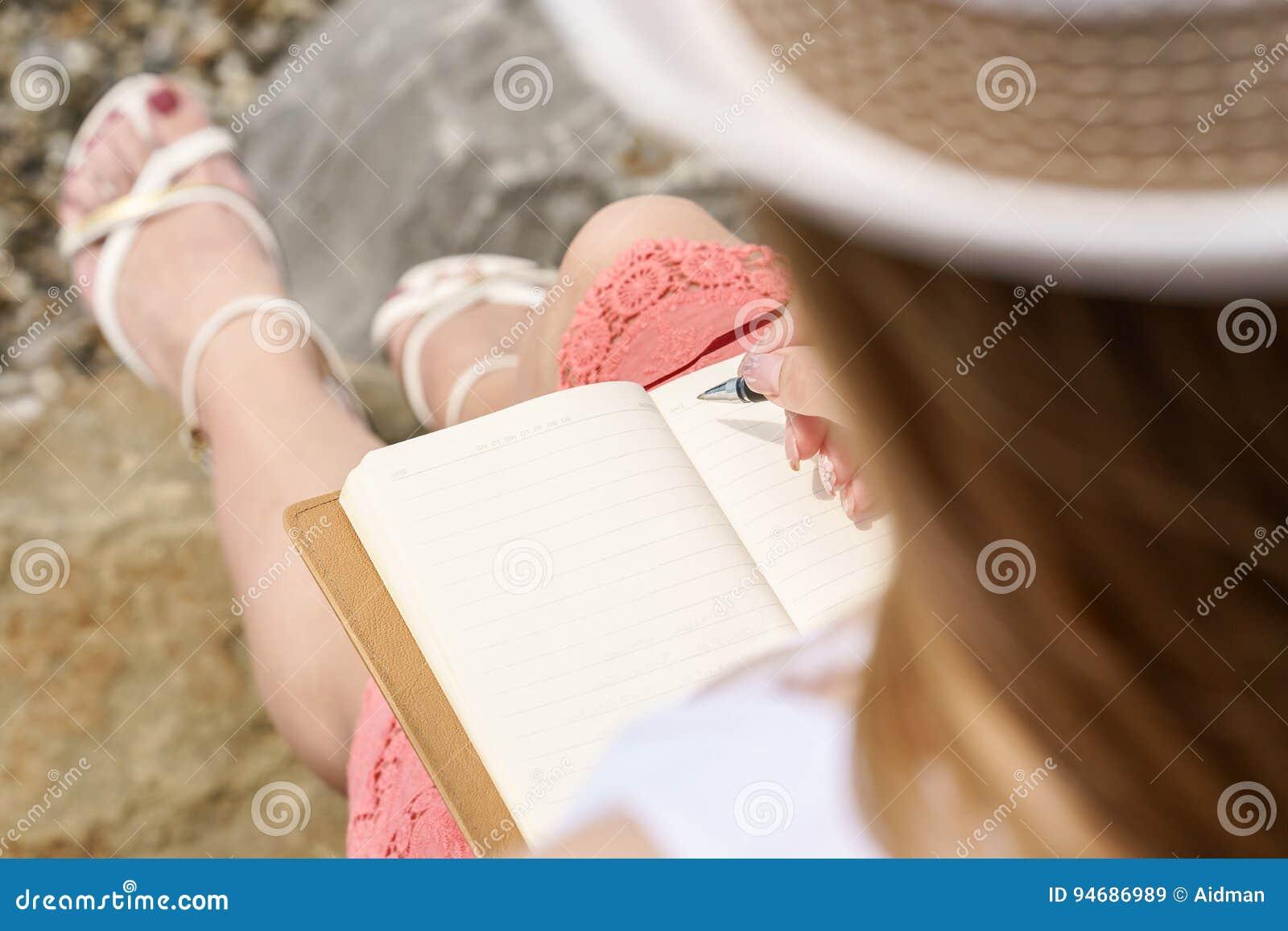 En nätt europeisk kvinna är sittinen på en sten c och att skriva något idé, brev eller jobb vid pennan i hennes anmärkningsbok