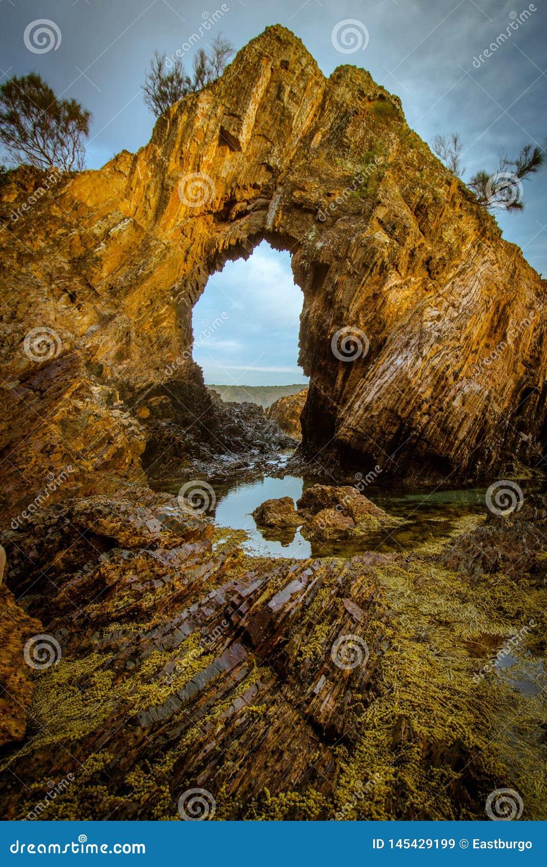 En naturlig båge på kusten på den guld- timmen