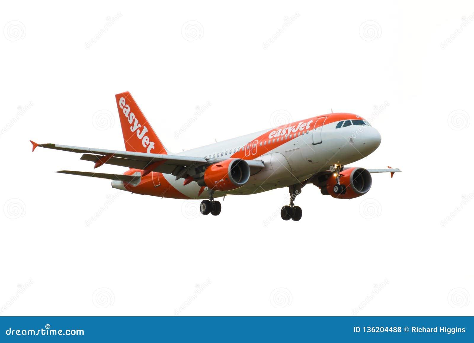 En nivå för easyJetflygbolagflygbuss A319-100 kommer in att landa på den London Gatwick flygplatsen bakgrund isolerad white