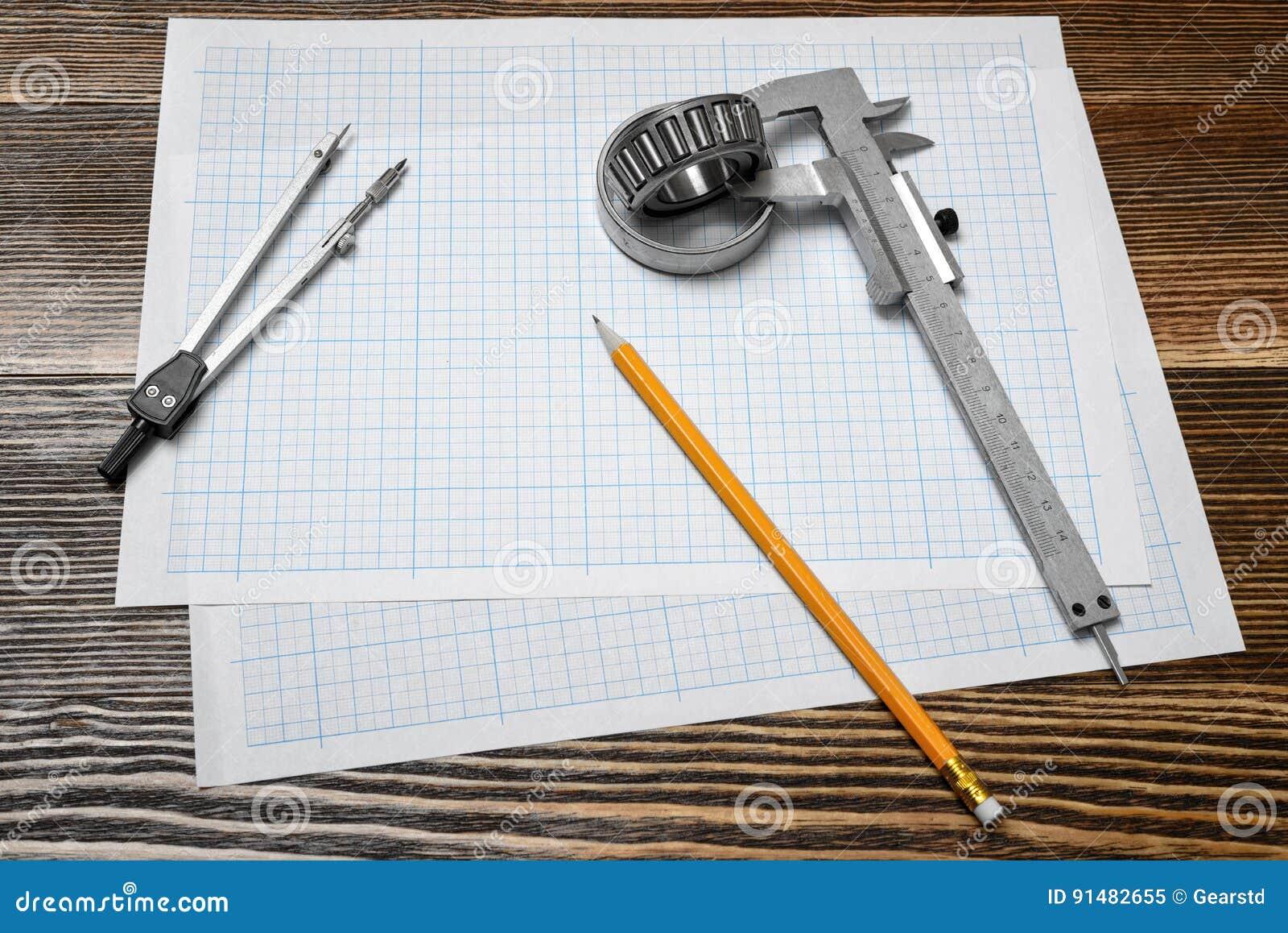 En nonieskalaklämma som rymmer ett lager, en blyertspenna och ett par av passare som ligger över skissning, skyler över brister p