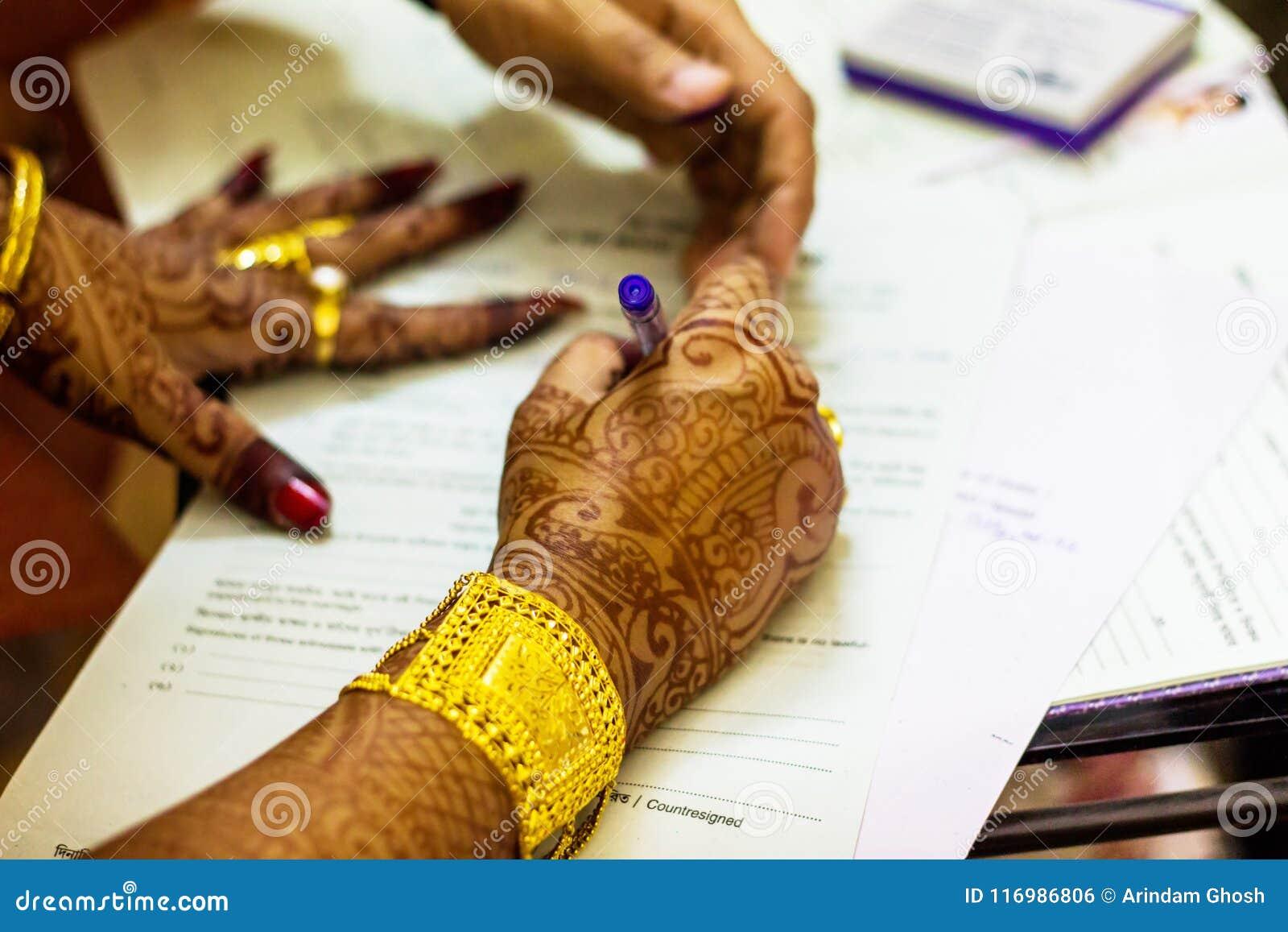En nyligen gift indisk bengali fru med den guld- för förbindelseregistrering för prydnad och för blacelet undertecknande formen