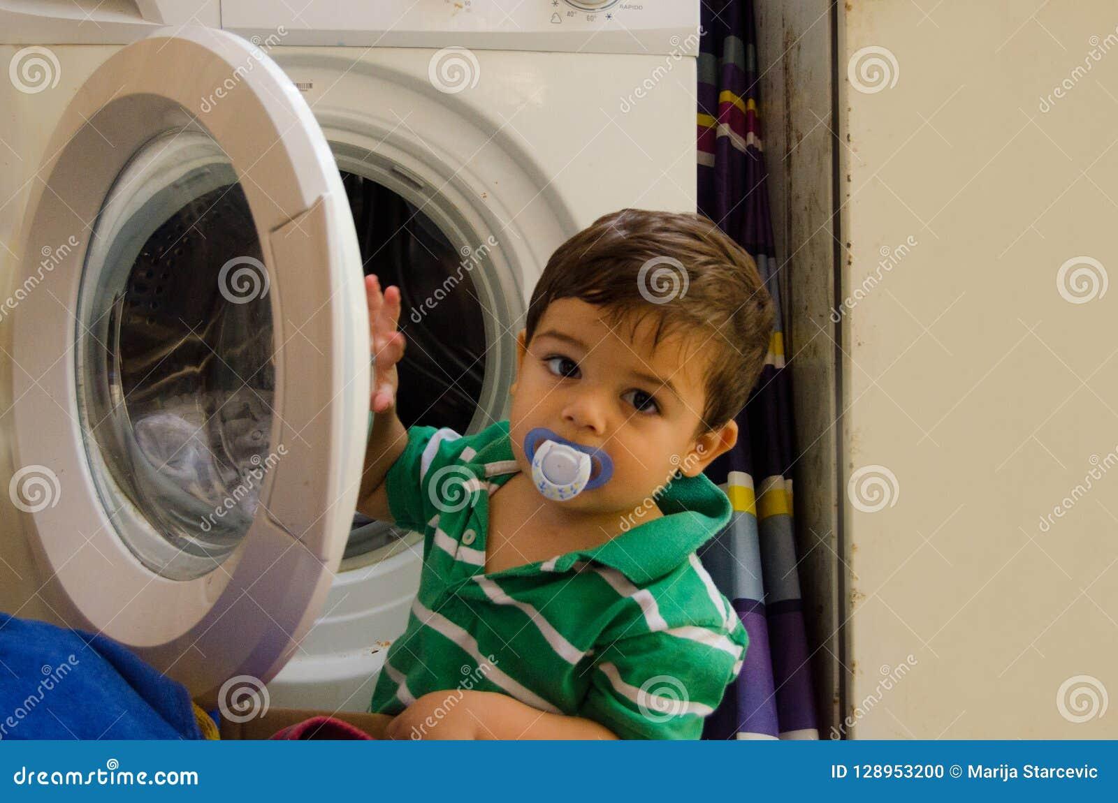 En och de gamla halva åren behandla som ett barn pojken som sätter kläder i tvagningmaskin