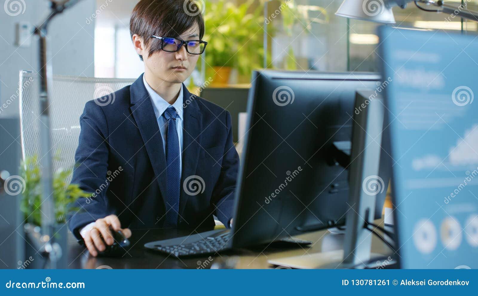 En oficina el hombre de negocios asiático del este trabaja en una mesa personal