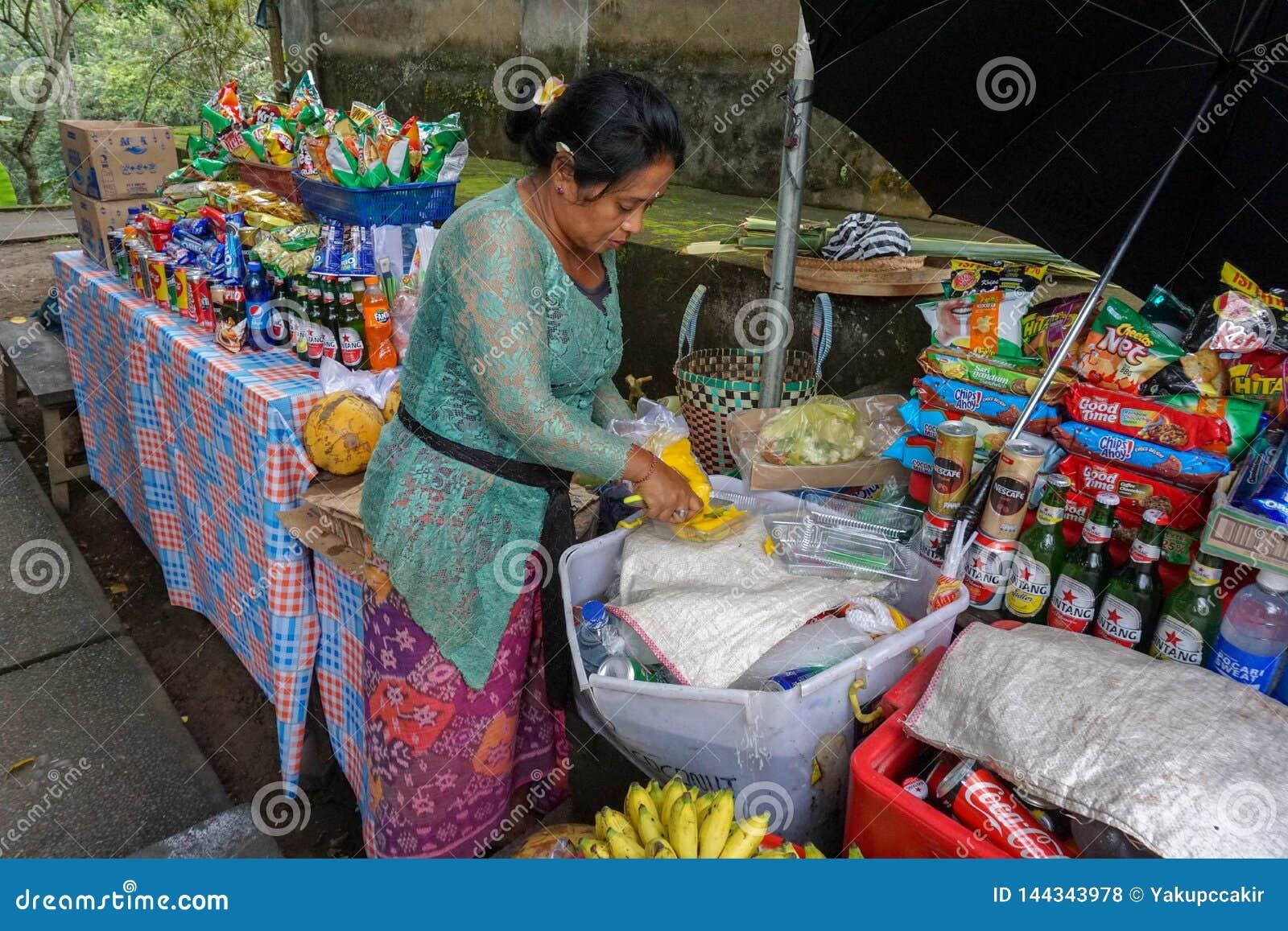 En oidentifierad asiatisk försäljare som säljer tropisk exotisk ny frukt på gatan, Bali, Indonesien, 11 08 2018