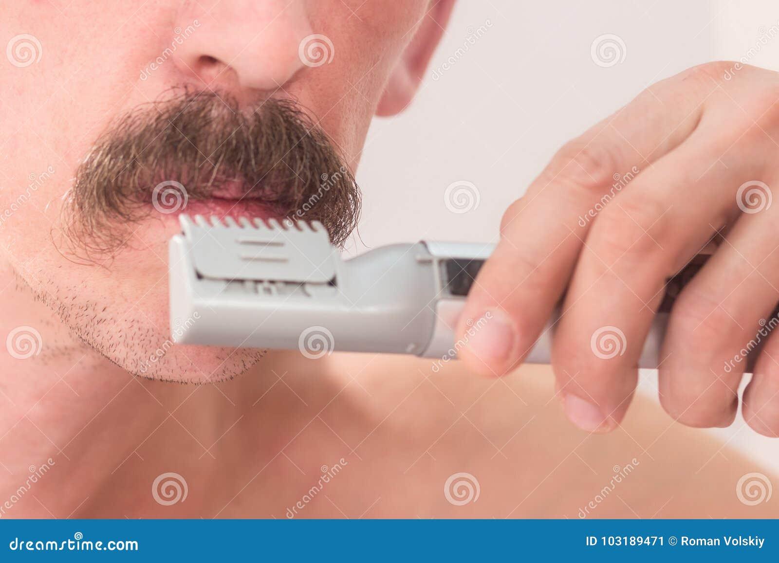 En orakad man klipper hans mustasch med en beskärare Närbild