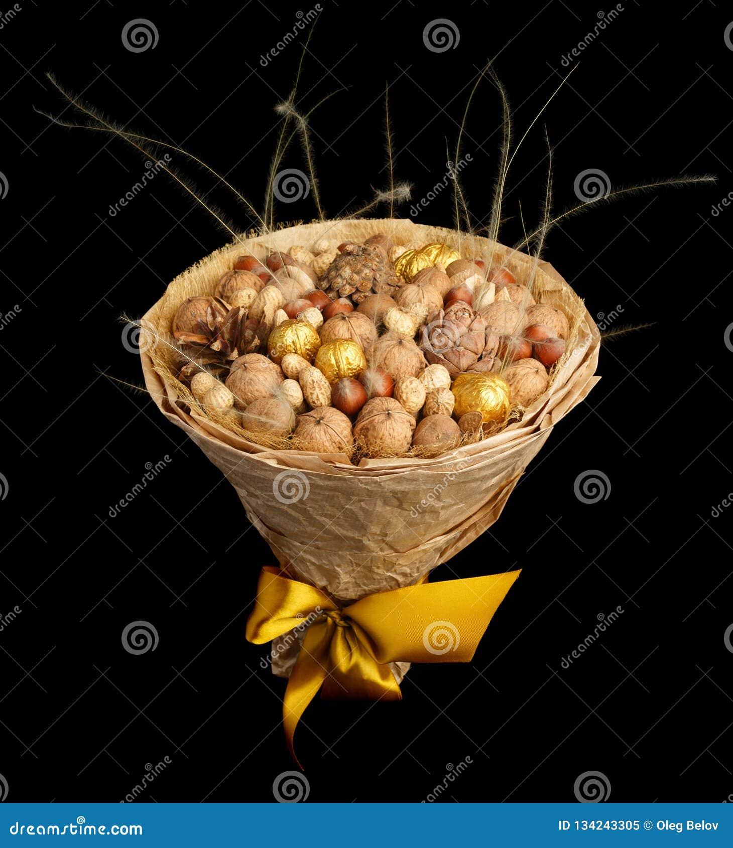 En original- gåva i form av en bukett som består av olika muttrar och kottar som slås in med kraft papper och binds med en gul sa