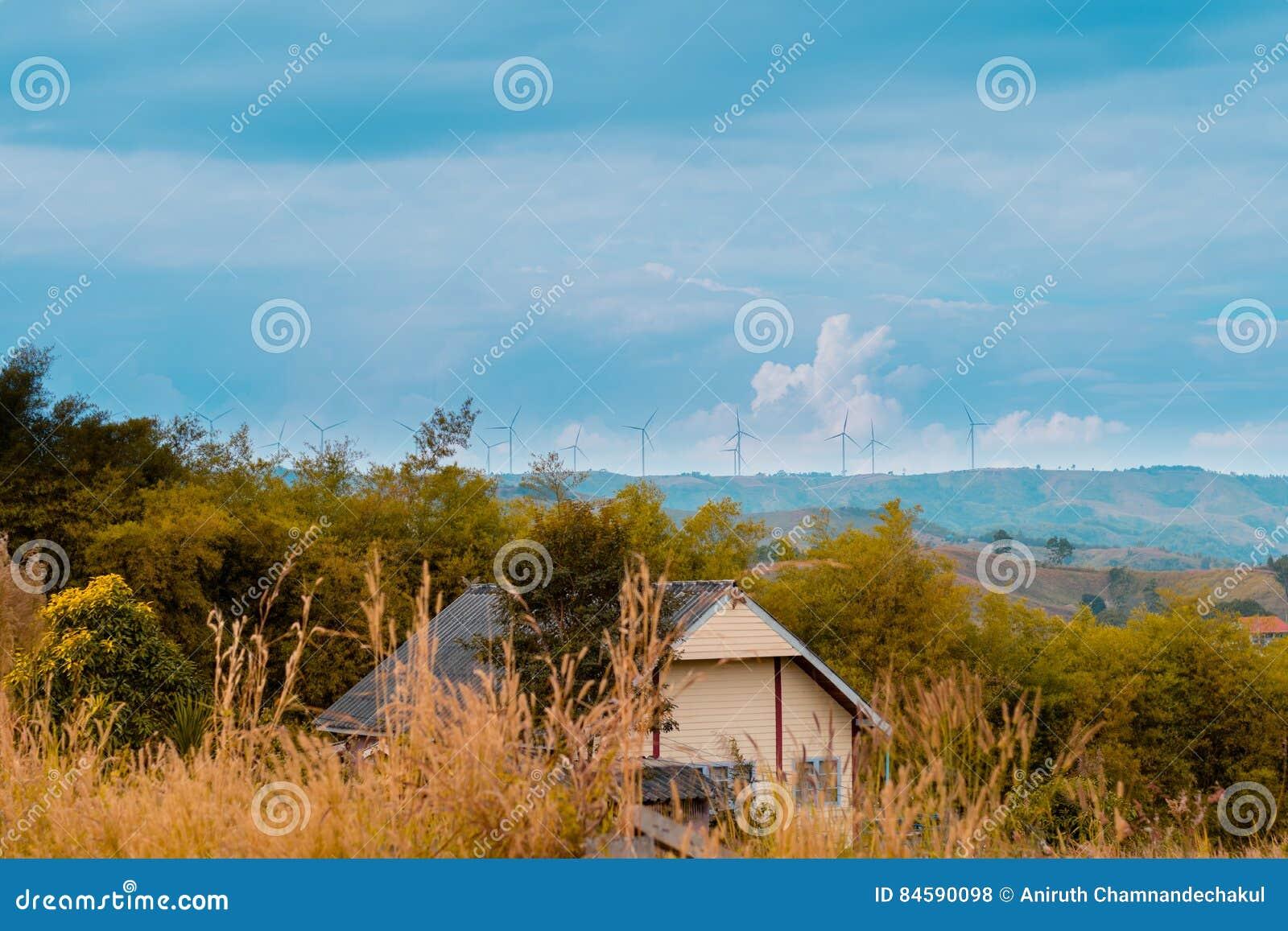 En otoño, turbinas y casa de viento en el prado