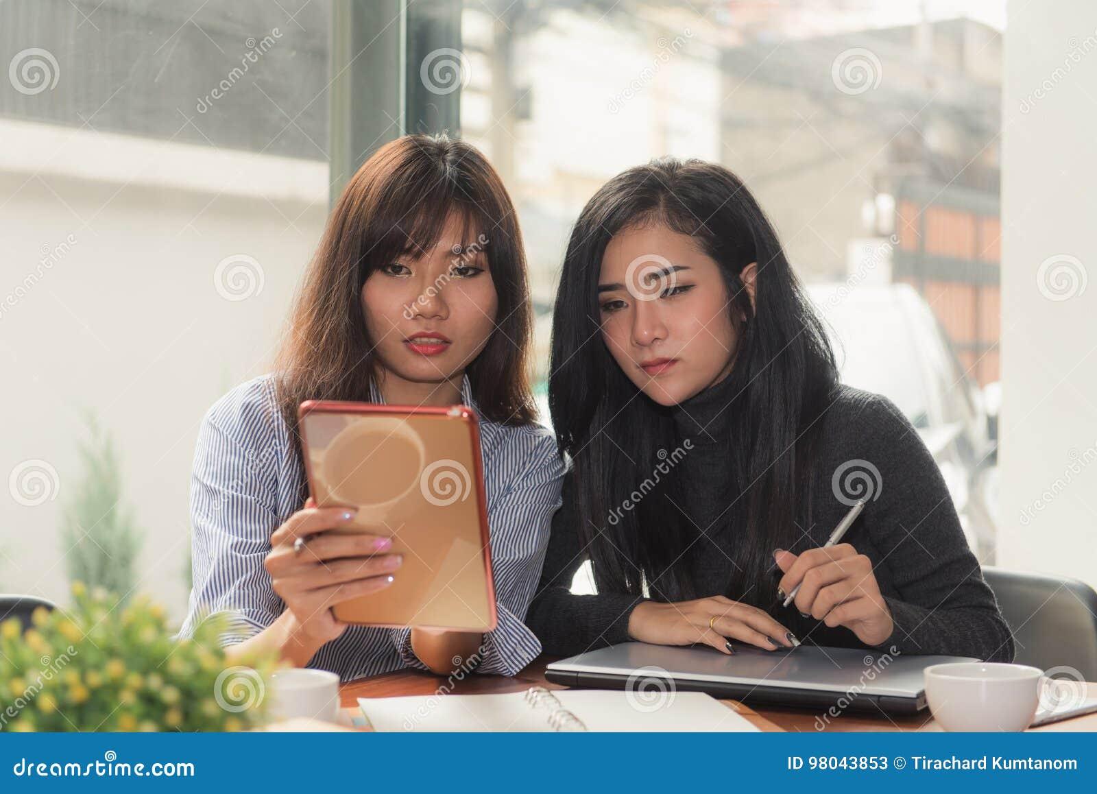 En-på-en möte Två unga affärskvinnor som sitter på tabellen i kafé Flickan visar information om kollega på bärbar datorskärmen