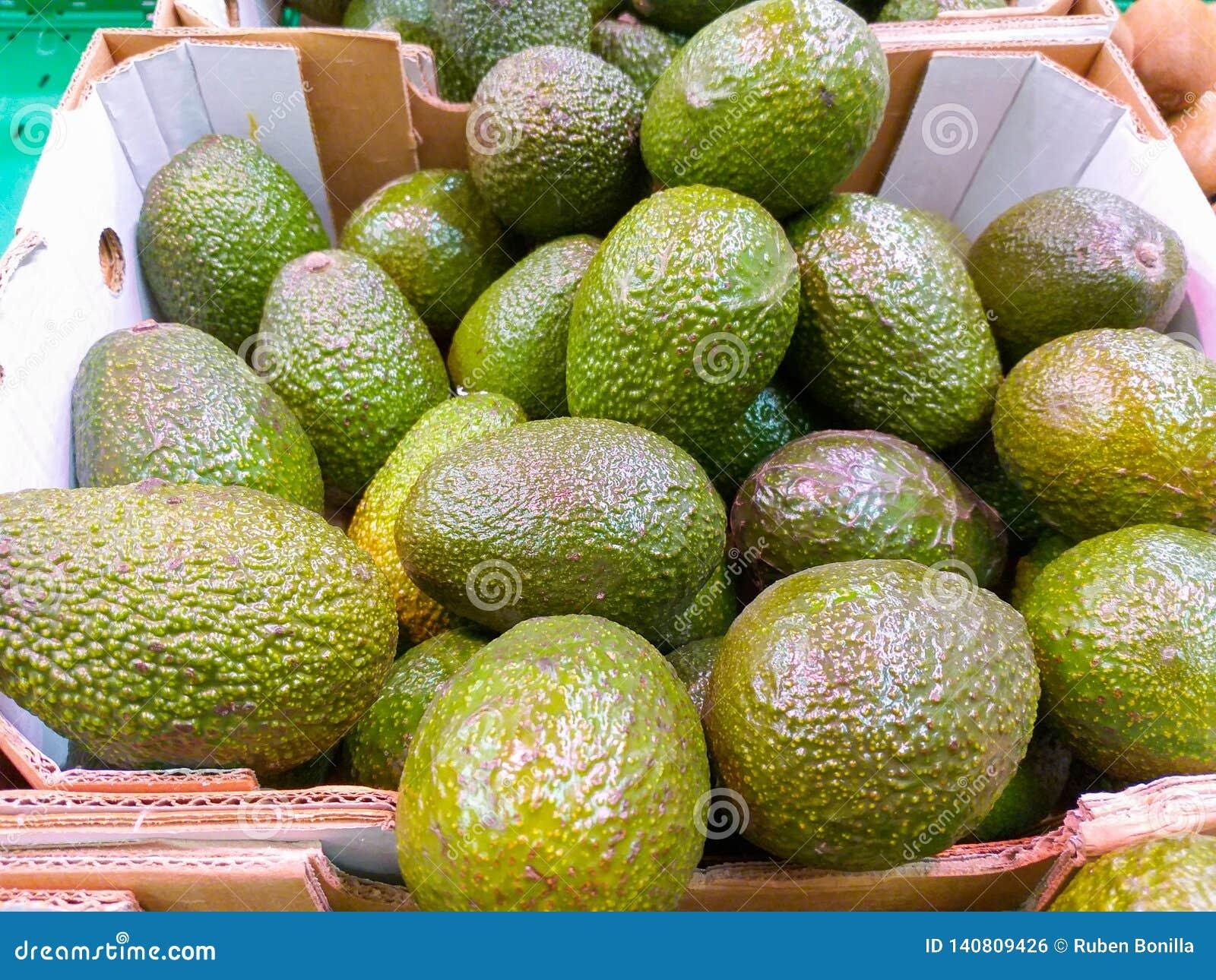 En paperboardask på marknadsöverflödet av smakliga briljanta gröna avokadon skördade precis klart att säljas till kunder