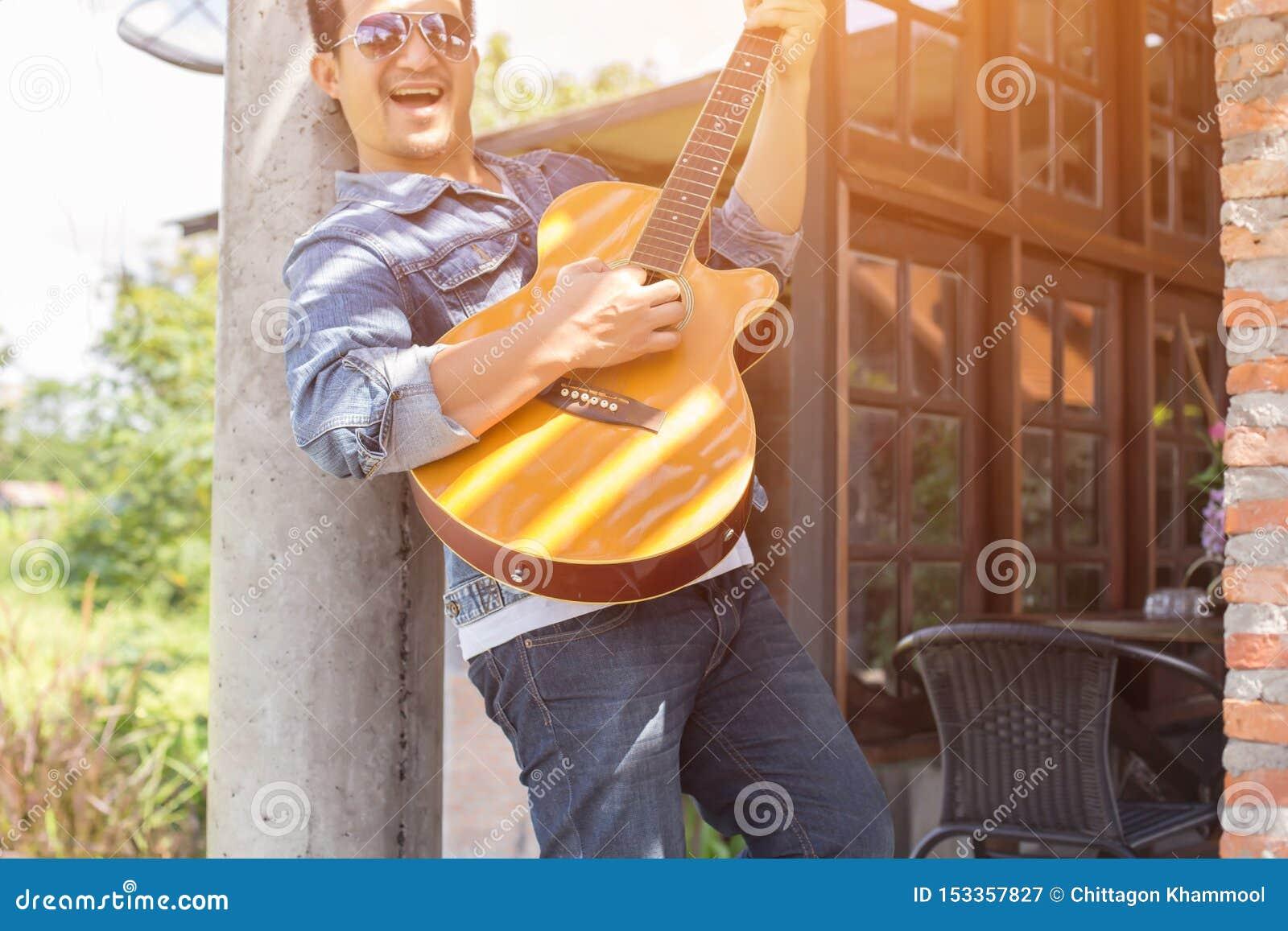 En parc, heureux pratiqu?s jeune la guitare de hippie par homme et ont plaisir ? jouer la guitare