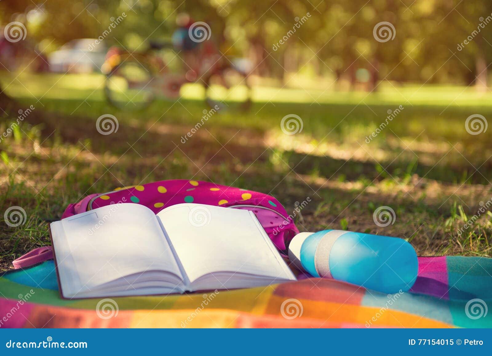 En parc se trouvant sur le livre, le sac à dos et la bouteille couvrants Bicyclette sur b